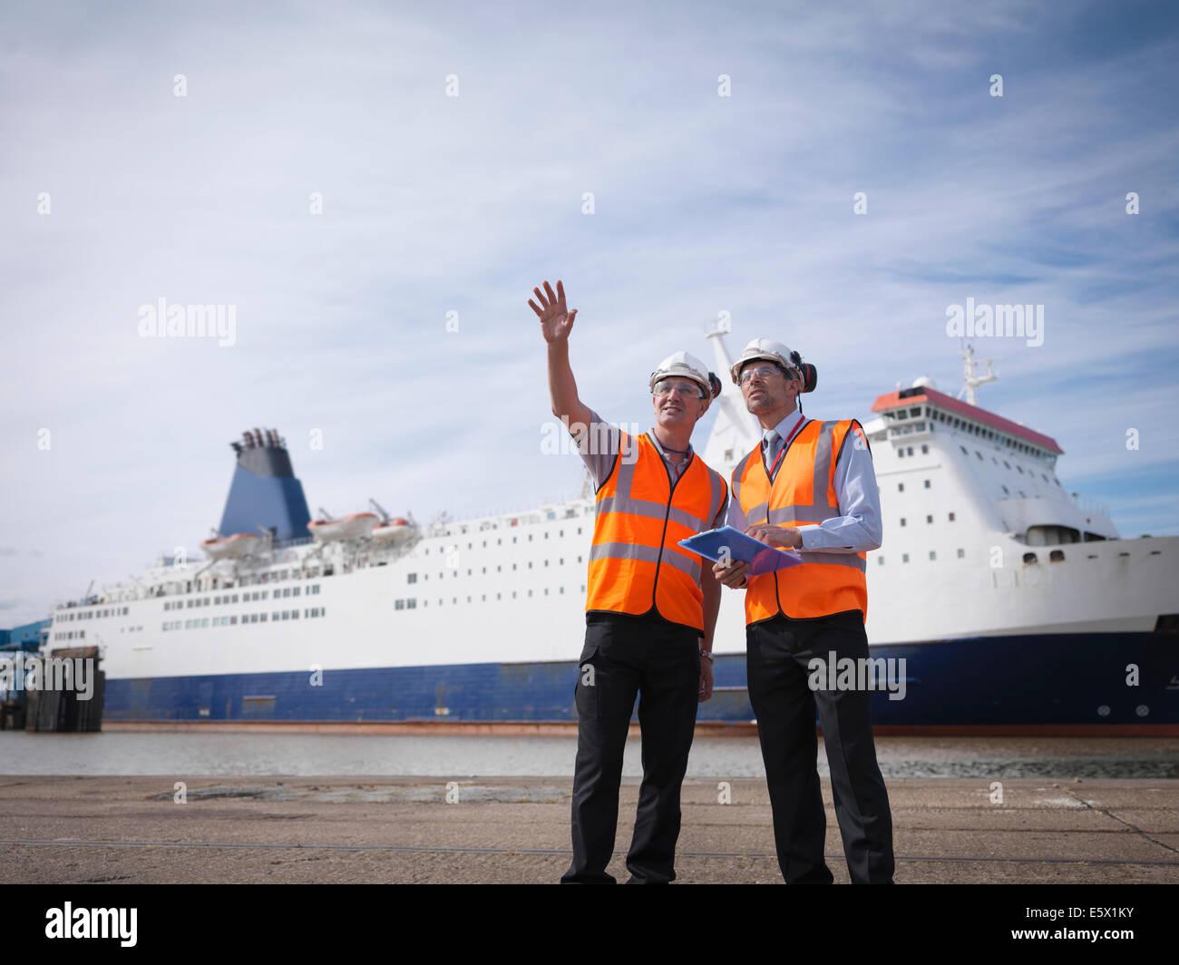 I lavoratori portuali con la nave in porto Immagini Stock
