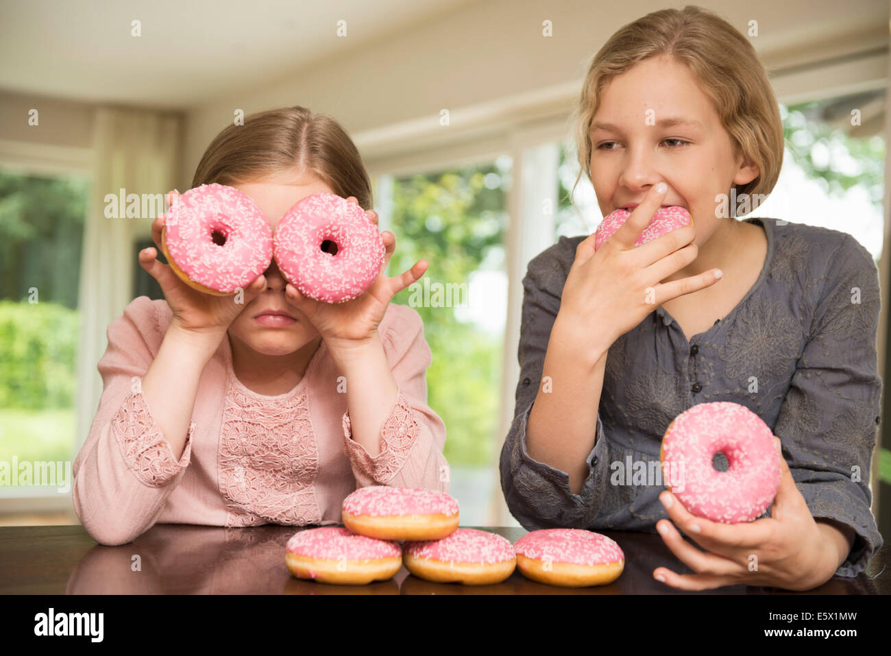 Due sorelle una ciambella con fori sui suoi occhi, le altre mangiare Immagini Stock