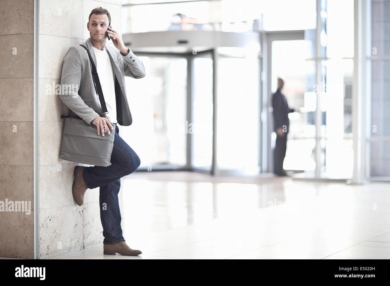 Giovane imprenditore chattare su smartphone nel centro congressi atrium Immagini Stock