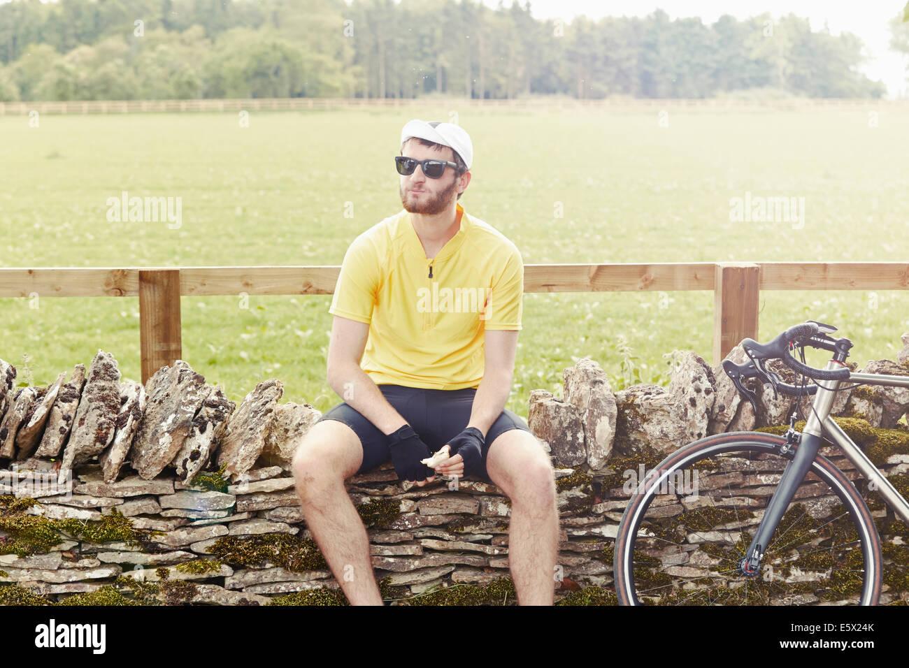Ciclista seduto sul muro di pietra, Cotswolds, REGNO UNITO Immagini Stock