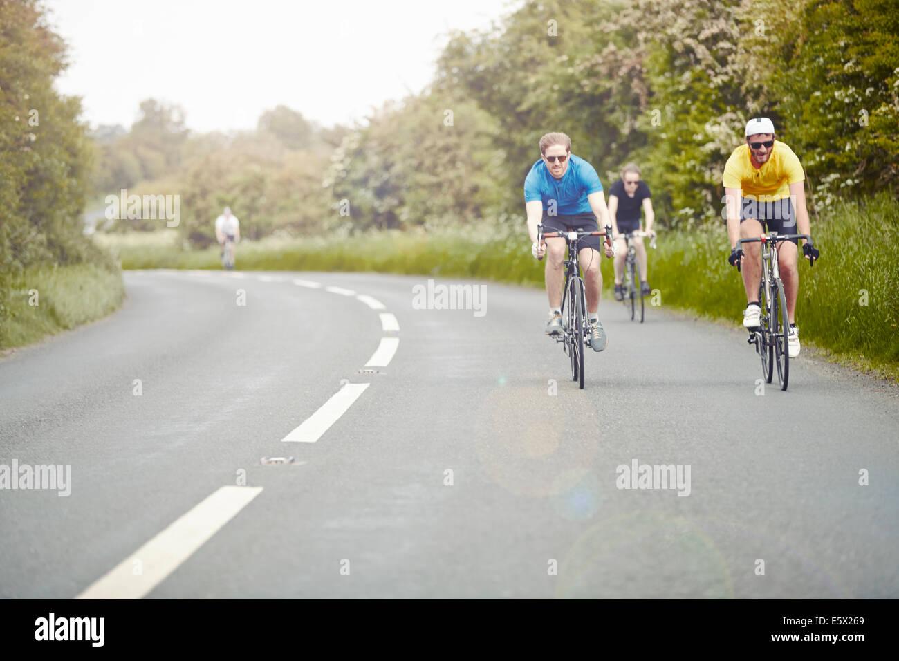 I ciclisti equitazione sulla strada a carreggiata singola, Cotswolds, REGNO UNITO Immagini Stock