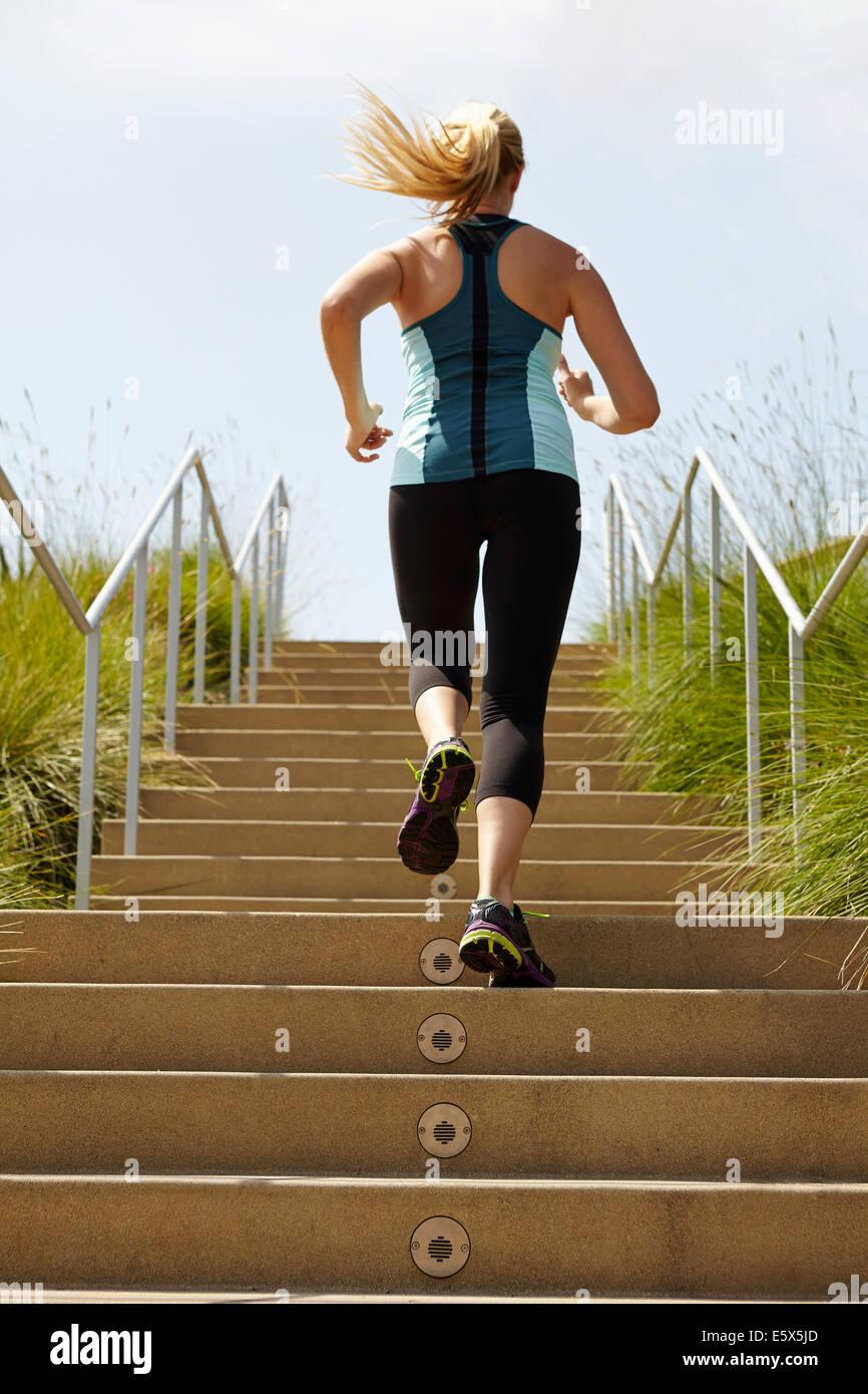 La donna in esecuzione su per le scale Immagini Stock