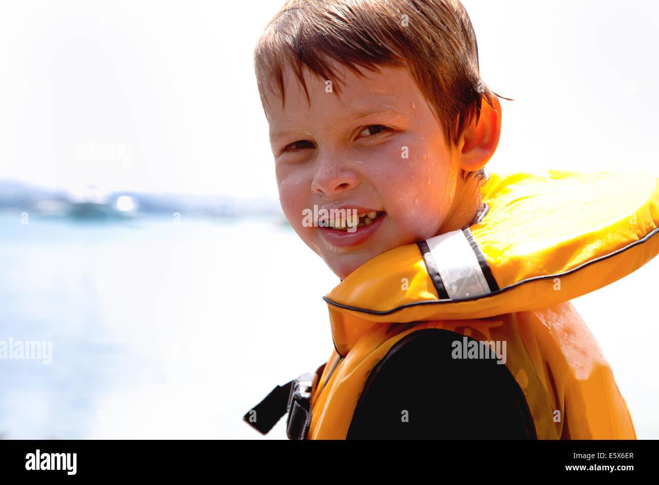 Close up ritratto di ragazzo sorridente nel giubbotto di salvataggio Immagini Stock