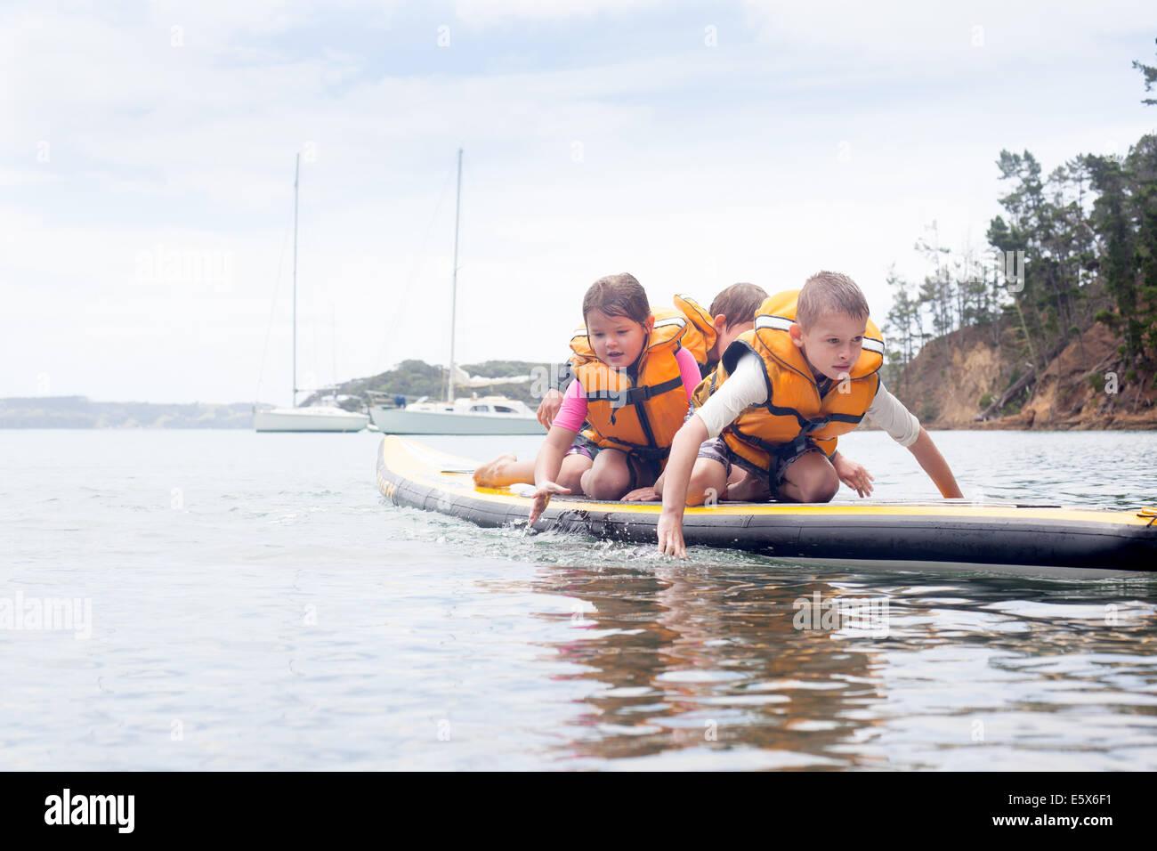 Fratelli e sorelle paddleboarding sulle ginocchia in mare Immagini Stock