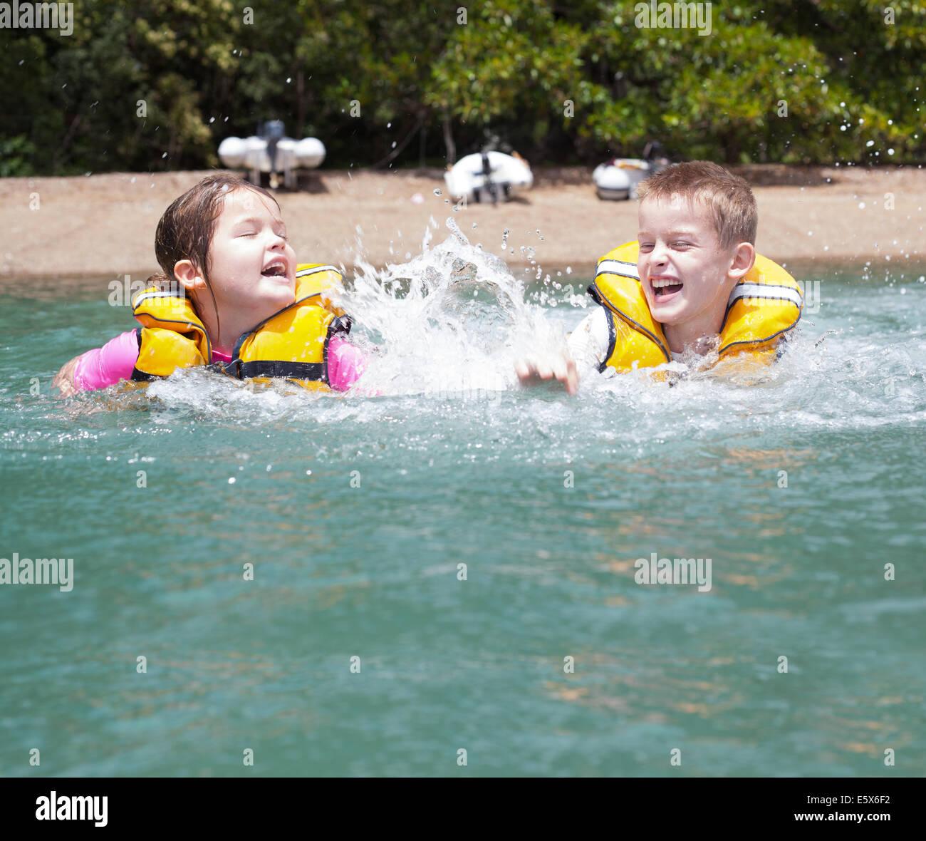 Fratello e Sorella gioca combattimenti e spruzzi in mare Immagini Stock