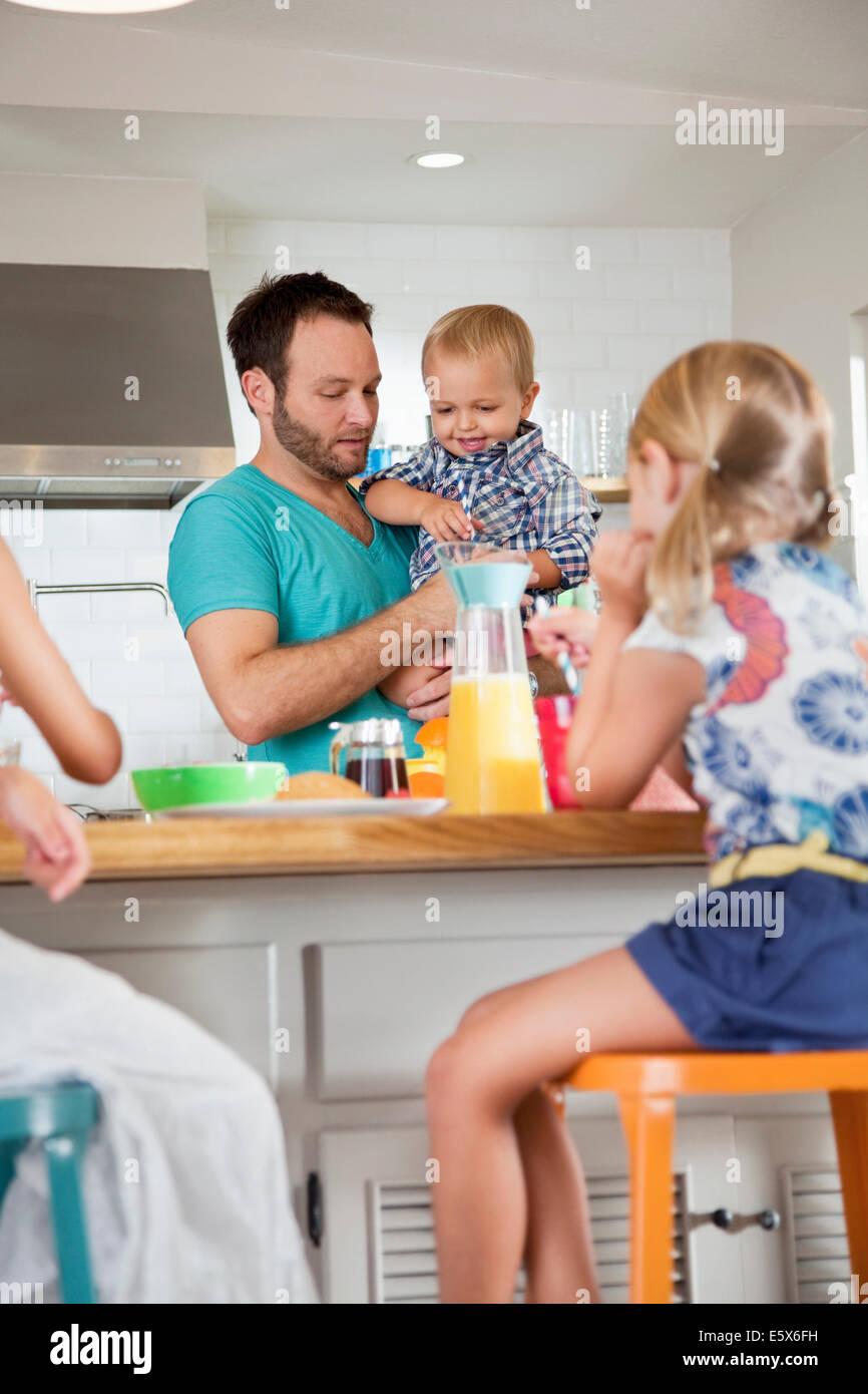 Padre multi tasking colazione con il figlio e le figlie Immagini Stock