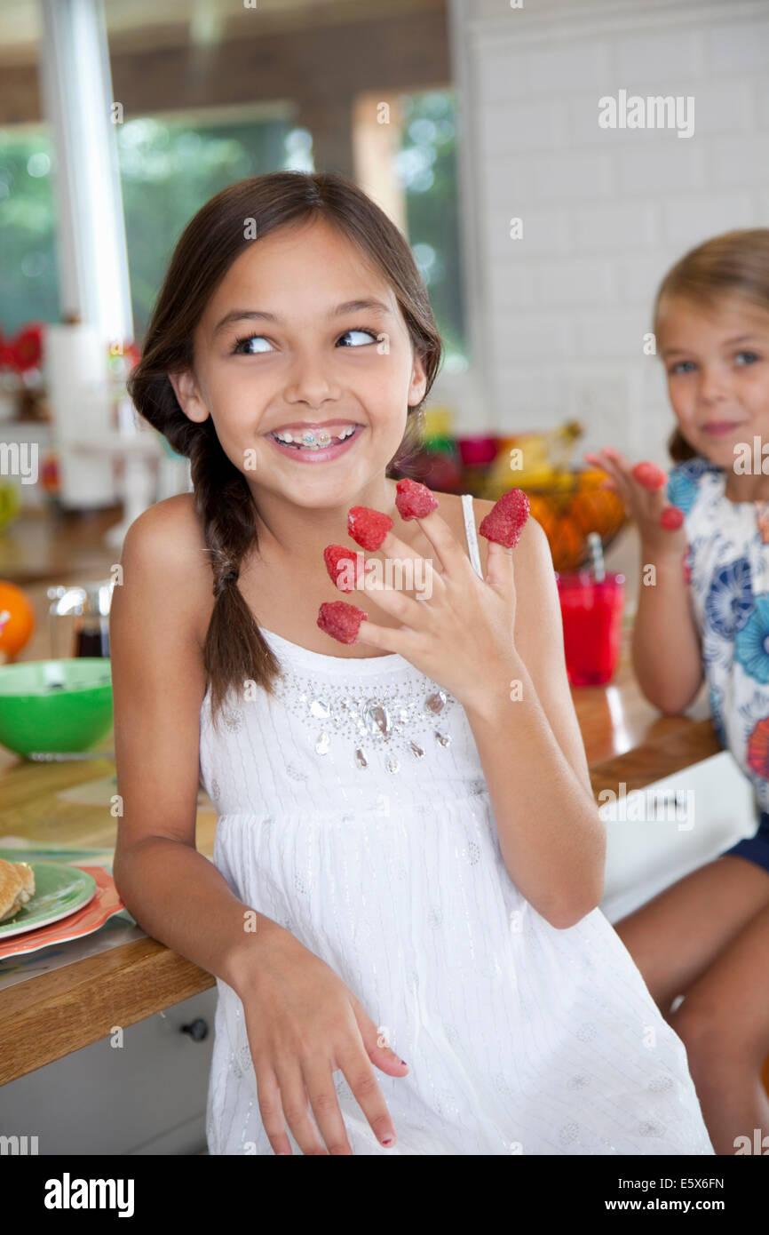 Due sorelle malizioso con lamponi sul loro dita in cucina Immagini Stock