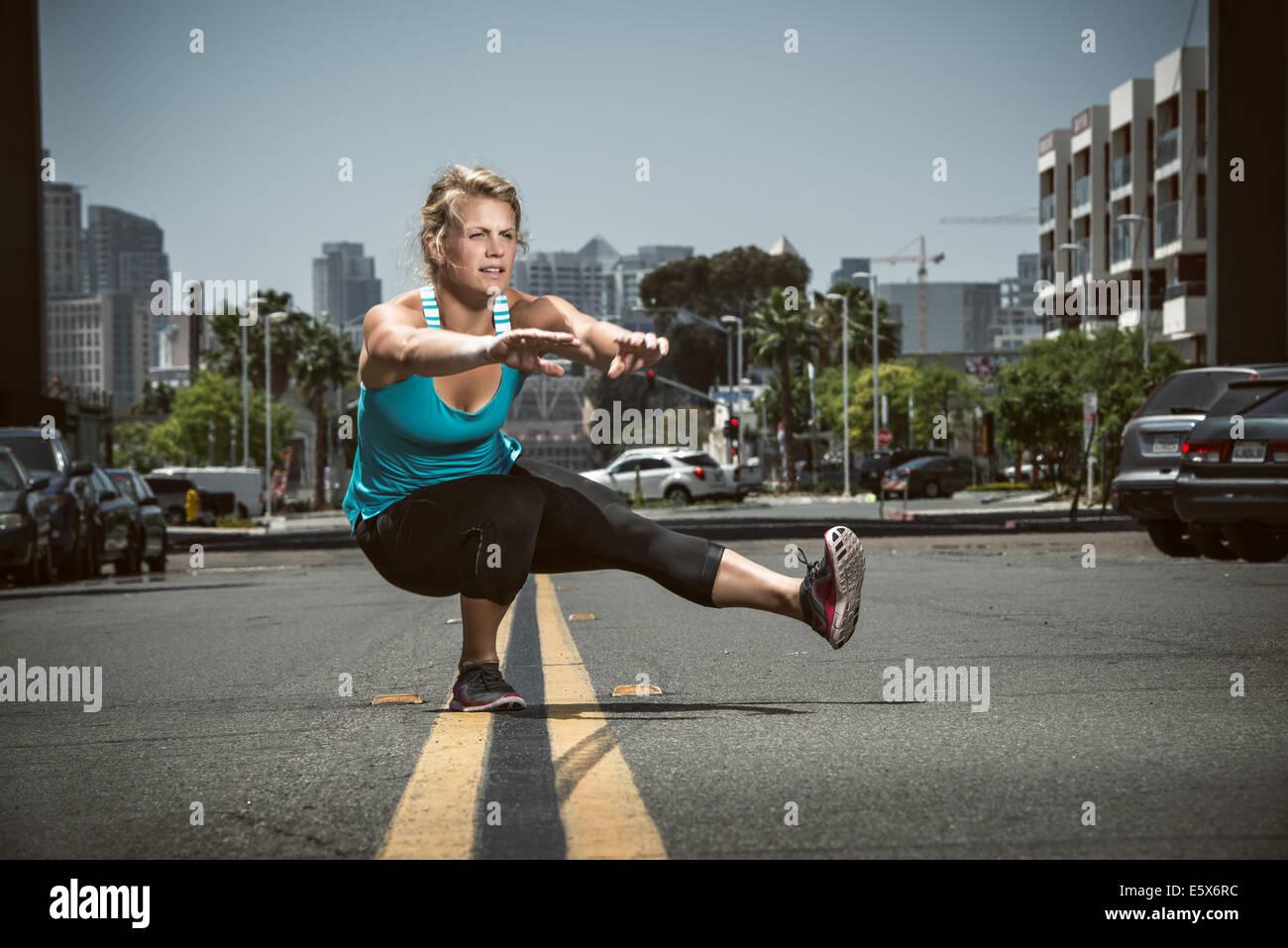 Giovane donna adulta in equilibrio su un piede in strada Immagini Stock