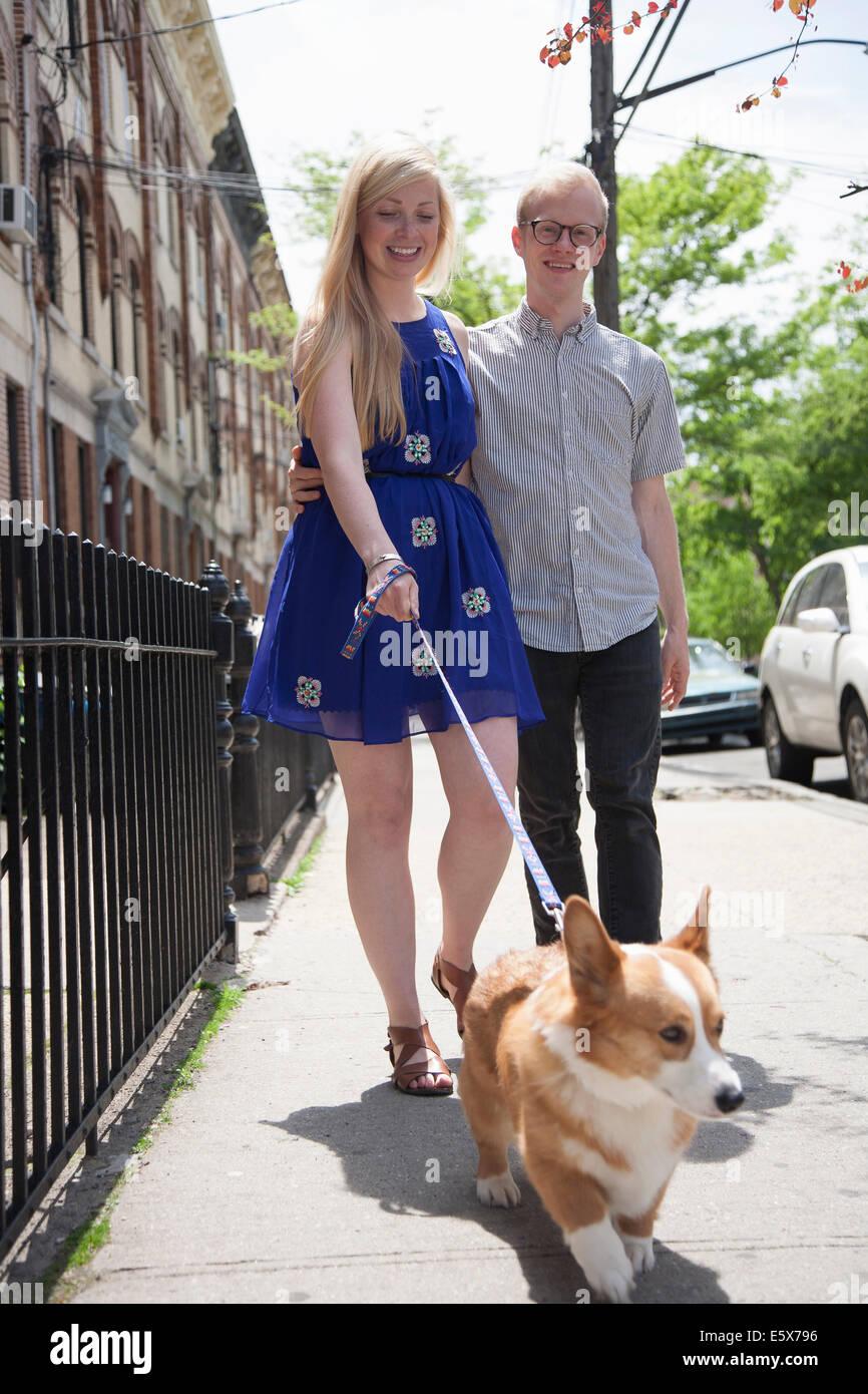 Coppia giovane tenendo corgi cane per una passeggiata lungo la strada Immagini Stock