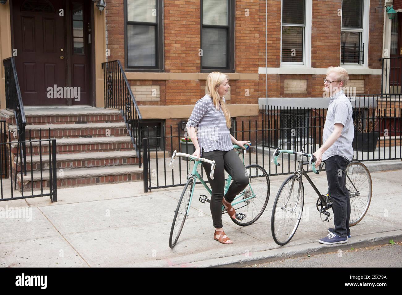 Coppia giovane con le biciclette in chat su strada Immagini Stock