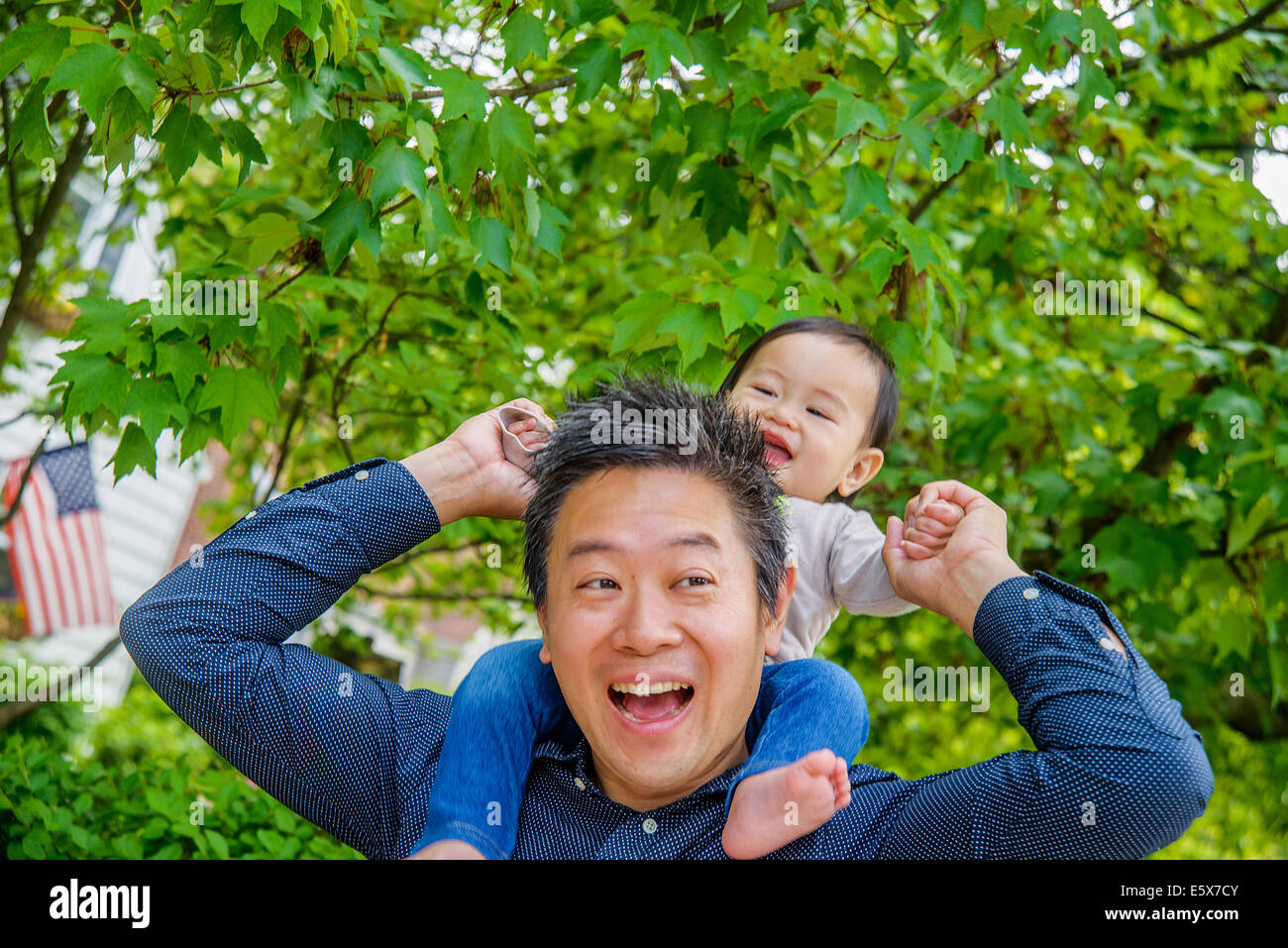 La metà degli adulti spalla padre bambino portando il figlio in giardino Foto Stock