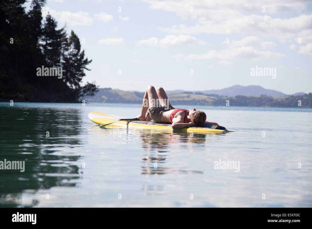 Metà donna adulta prendendo il sole sulla paddleboard in mare Immagini Stock