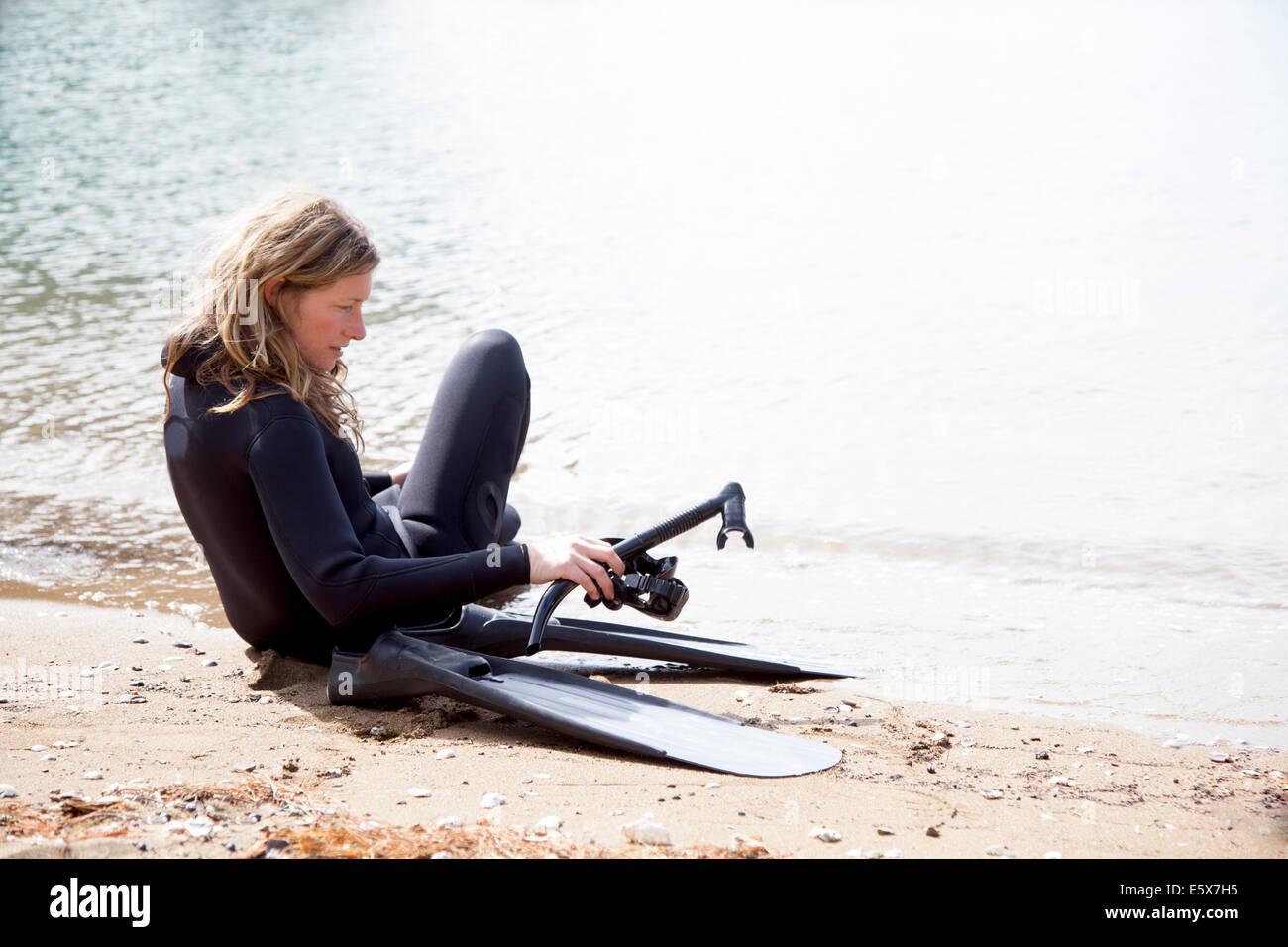 Metà femmina adulta scuba diver preparando a calarsi sulla spiaggia Immagini Stock