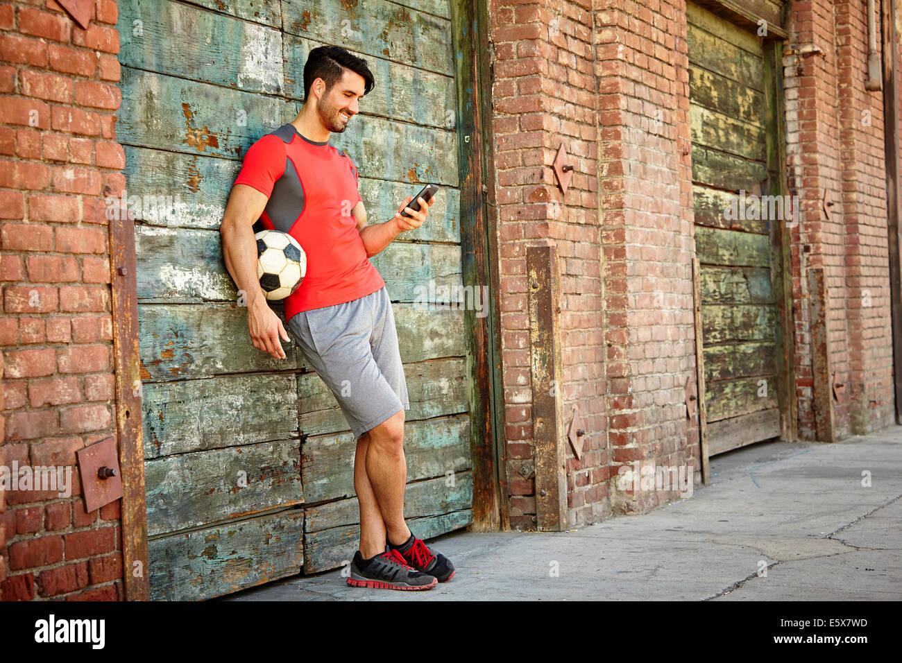 Maschio giovane giocatore di calcio texting sullo smartphone Immagini Stock