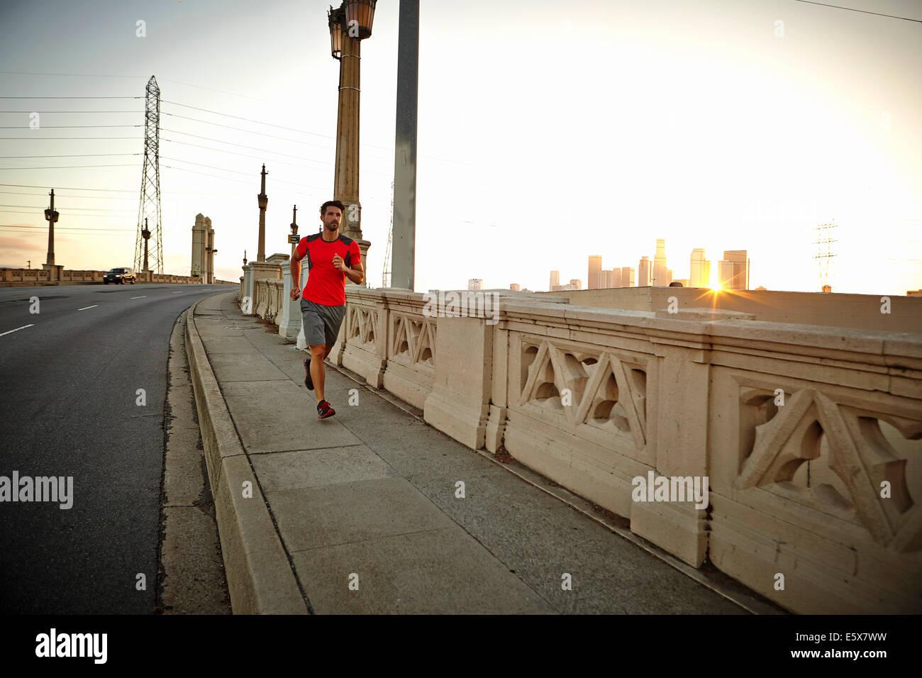 Giovane uomo che corre attraverso il ponte della città di sunrise Foto Stock