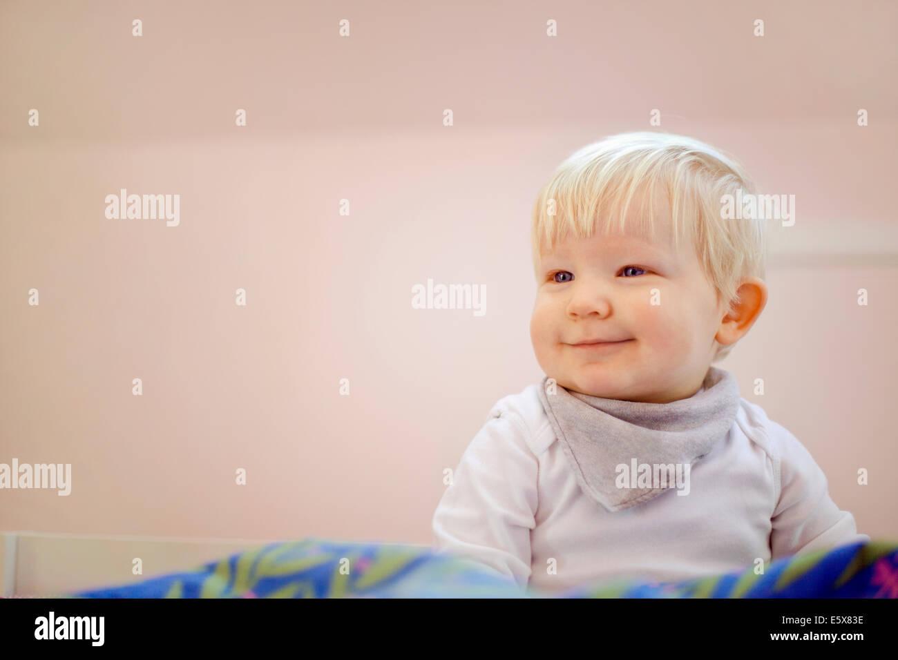 Ritratto di carino quattordici del mese precedente bambino seduto sul piumone Immagini Stock