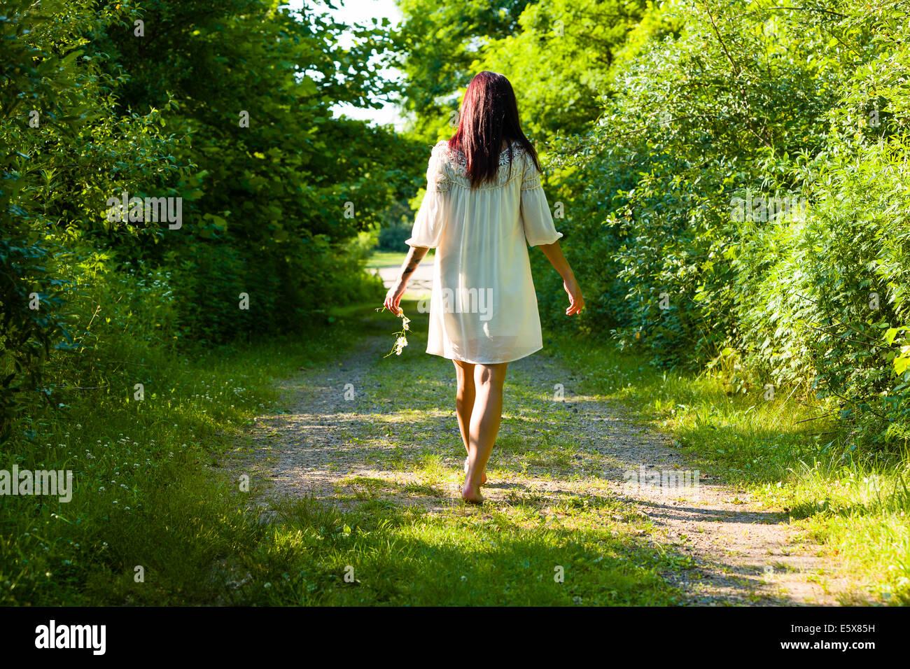 Vista posteriore del giovane donna passeggiando a piedi nudi lungo la pista rurale, Delaware Canal del parco statale Immagini Stock