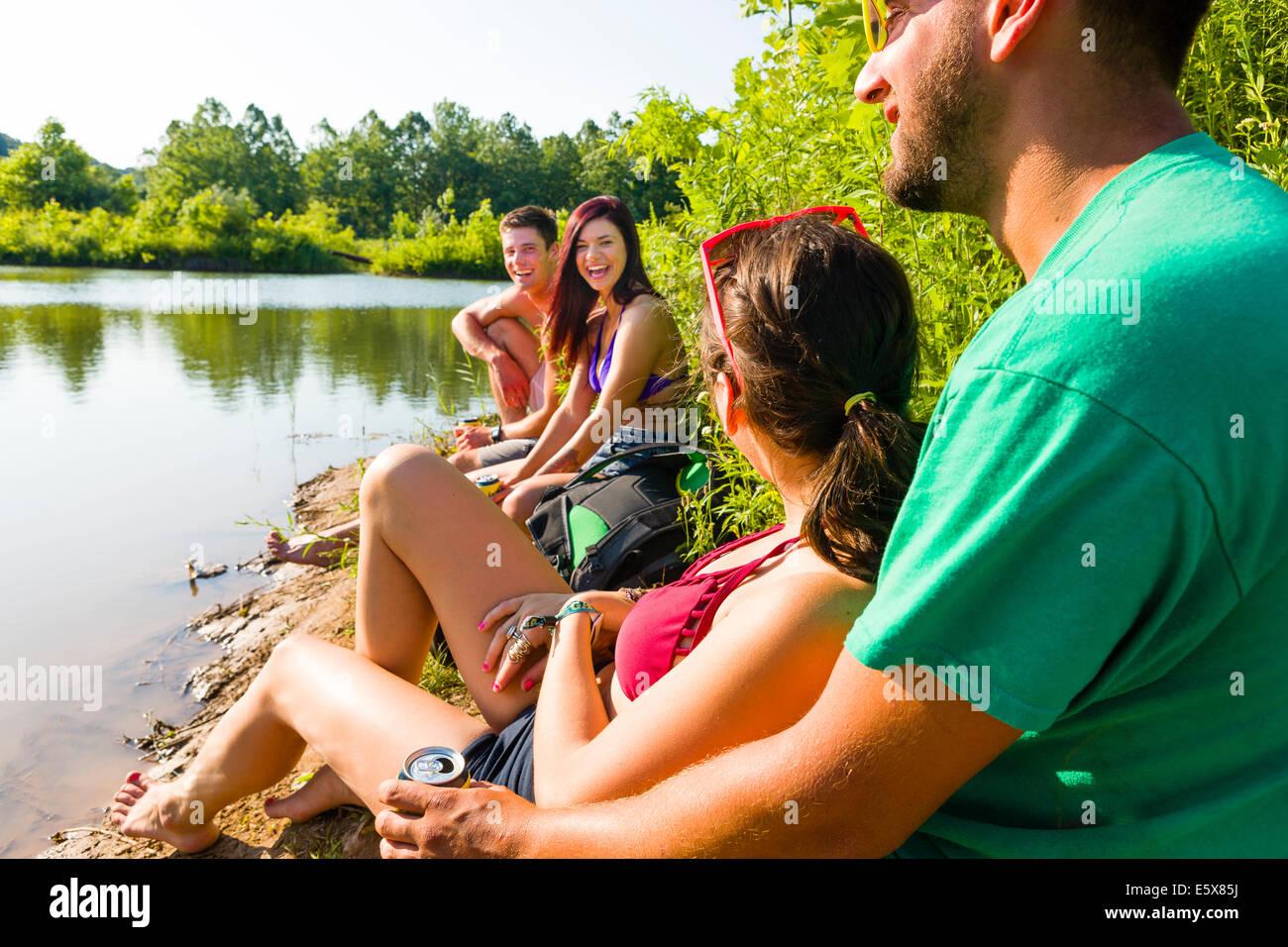 Due coppie giovani seduti sul canal bank, Delaware Canal del parco statale di nuova speranza, Pennsylvania, STATI Immagini Stock