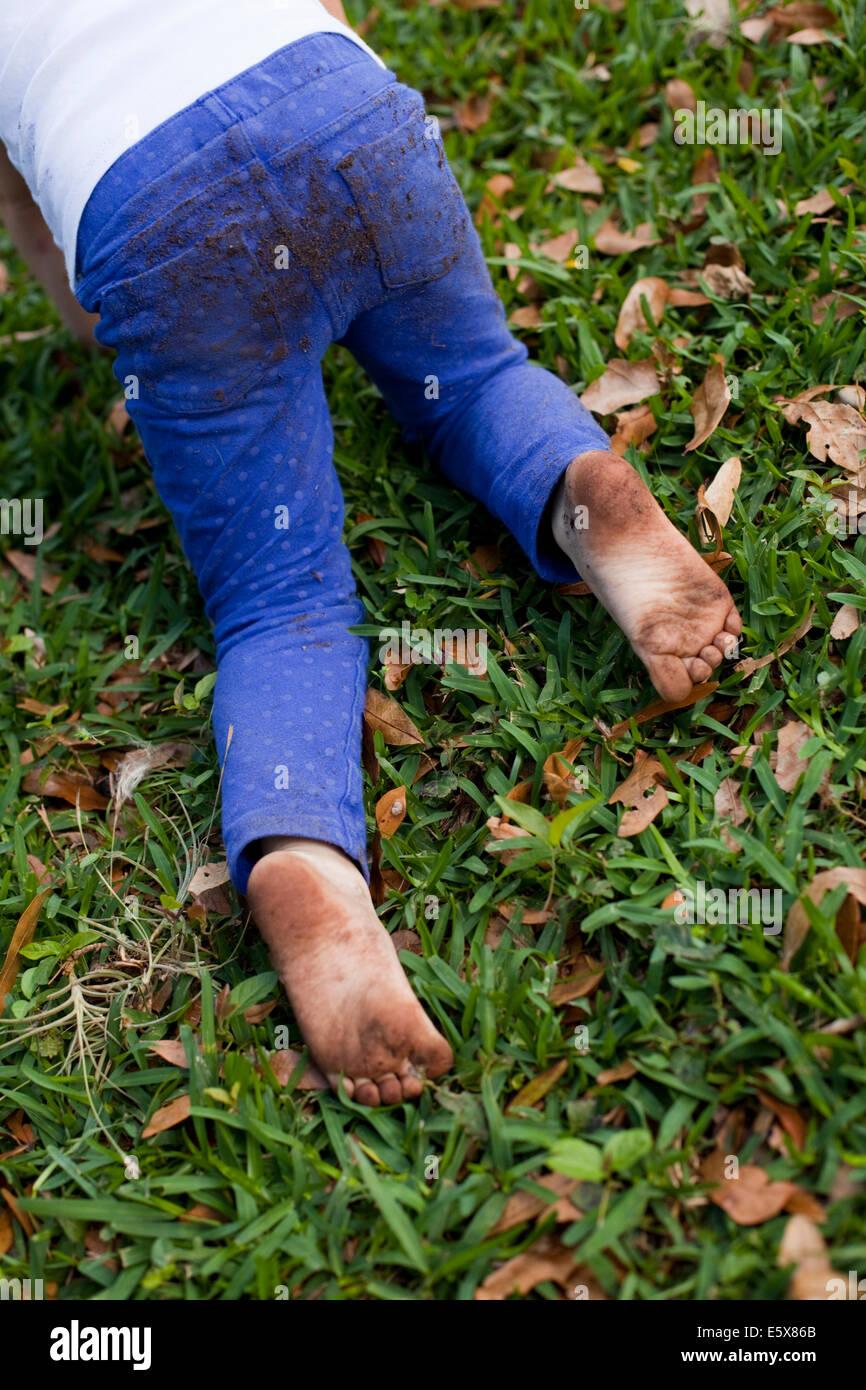 4 anno vecchia ragazza vita scende strisciando sul giardino di erba Immagini Stock