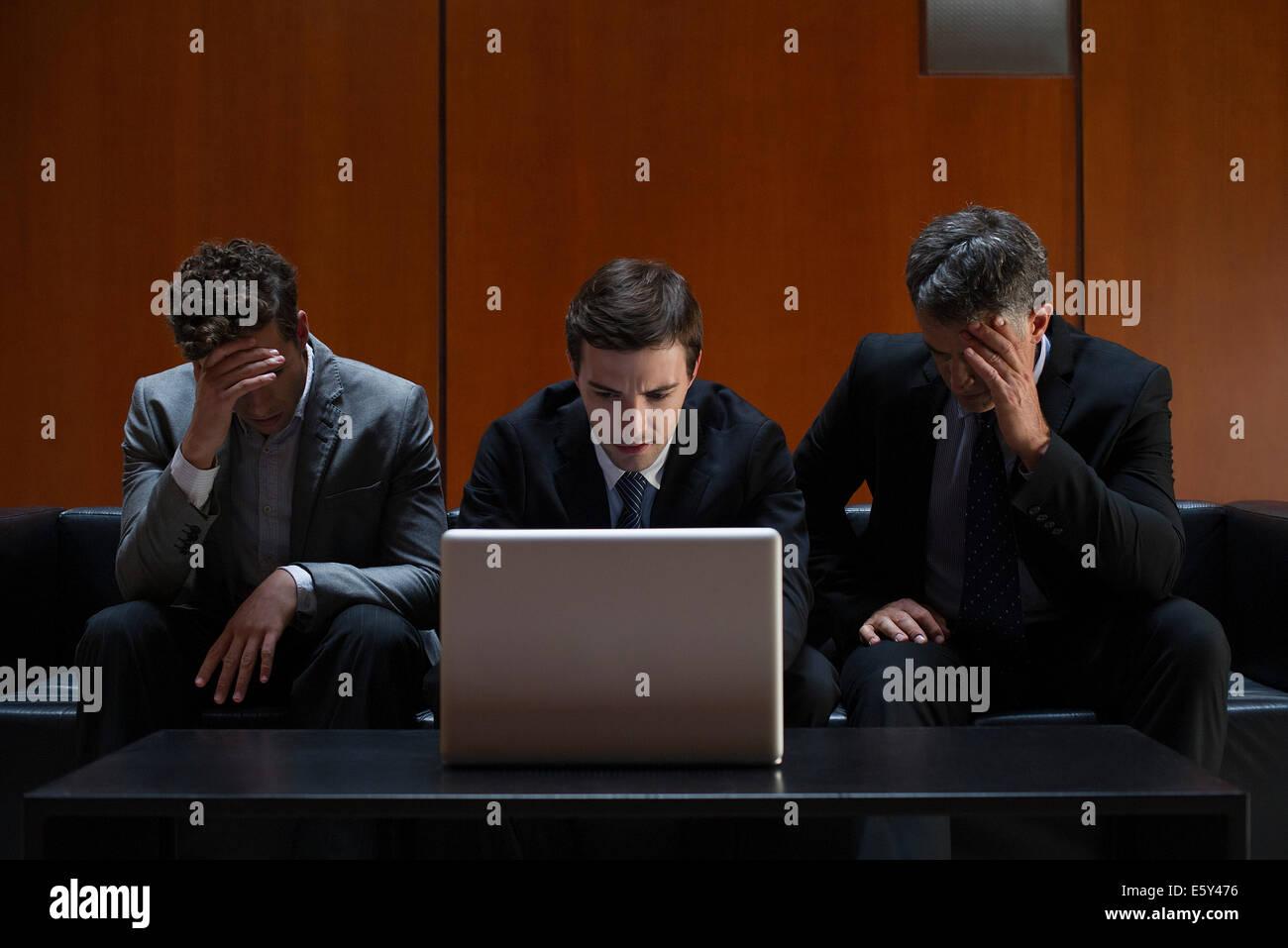 Deluso business associates seduti fianco a fianco sul divano guardando il computer portatile Immagini Stock