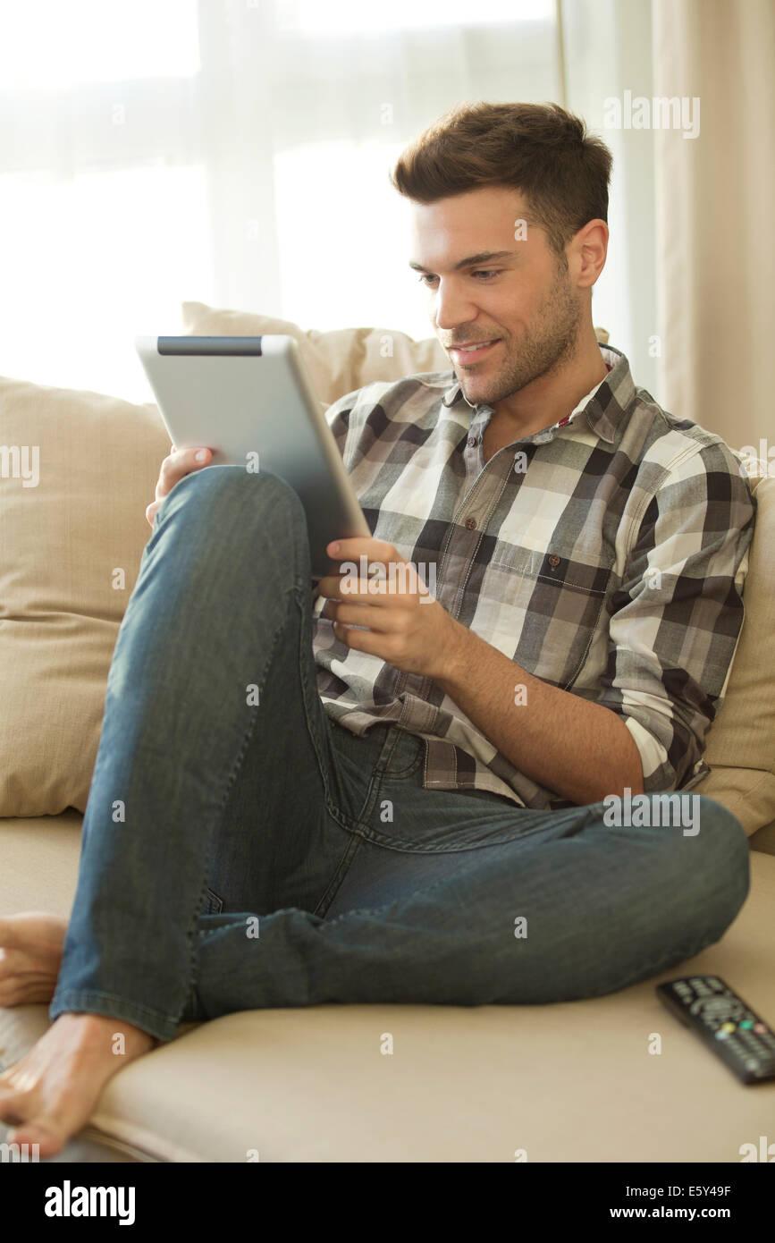 Giovane uomo con tavoletta digitale in casa Immagini Stock