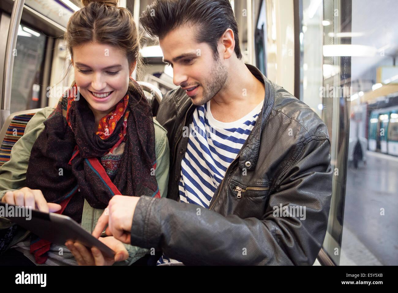 Coppia giovane in sella alla metropolitana guardando a tavoletta digitale insieme Immagini Stock