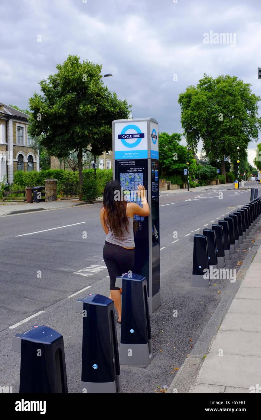 Giovane donna che guarda la mappa ciclo a vuoto il punto di noleggio in Haggerston, Londra Immagini Stock