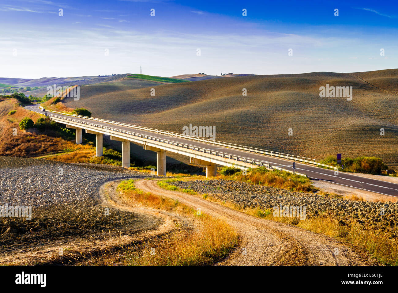 Ponte e colline in un giorno di estate nelle Crete Senesi in Toscana, Italia Immagini Stock