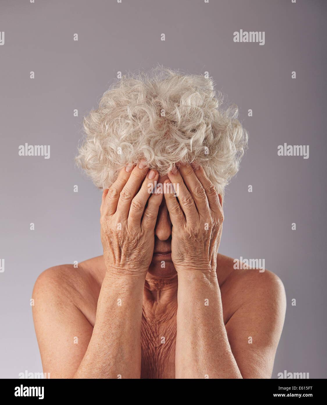 Ritratto di un sconvolto vecchia donna con la sua testa con le mani contro uno sfondo grigio. Triste donna senior Foto Stock