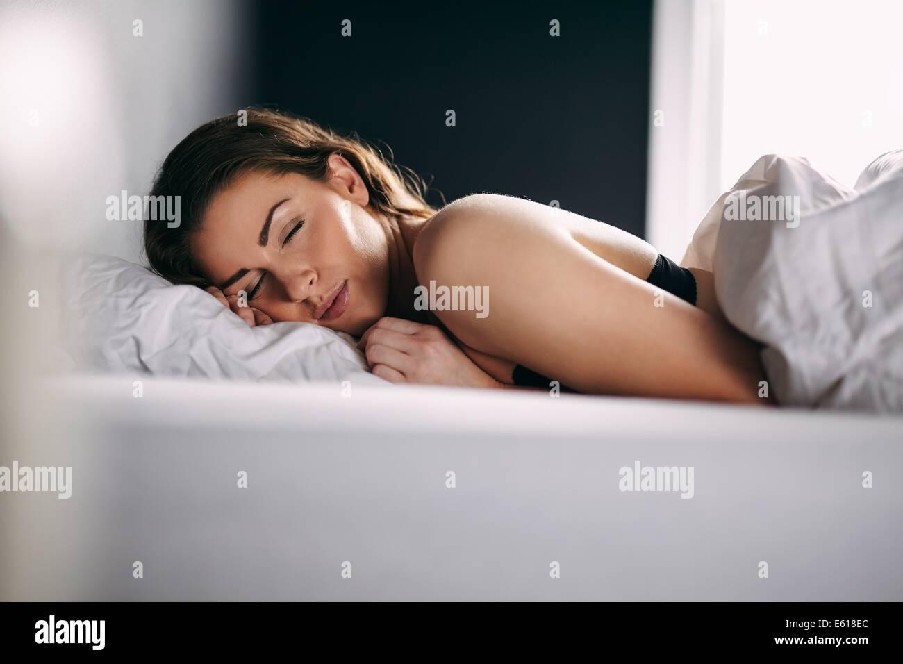 Ritratto di giovane rilassato lady dormire nel suo letto. Modello femminile dormire serenamente nel suo letto. Immagini Stock