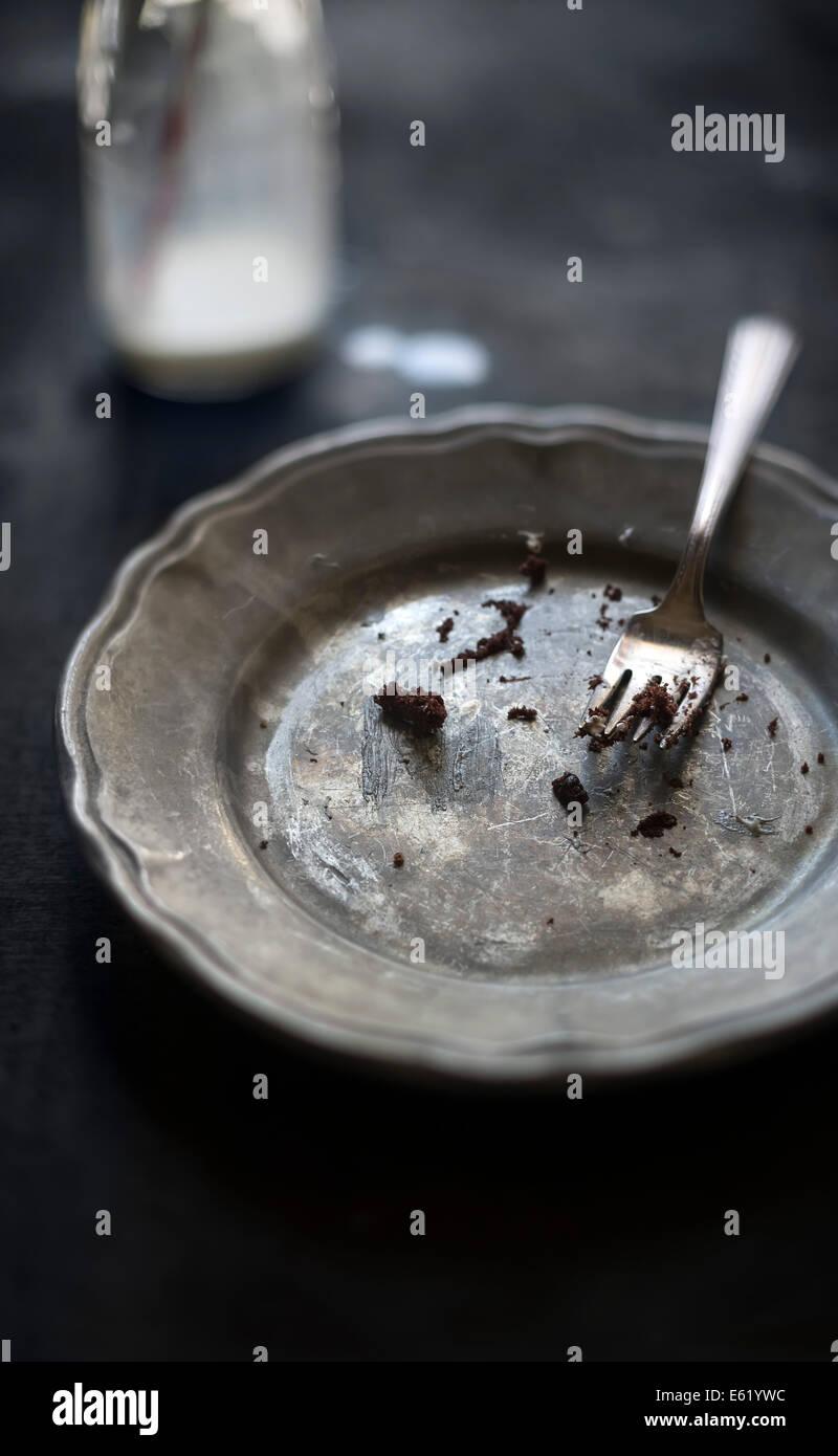 Piatto da dessert con cioccolato solo briciole sulla piastra. Bicchiere di latte in background al di fuori della Immagini Stock