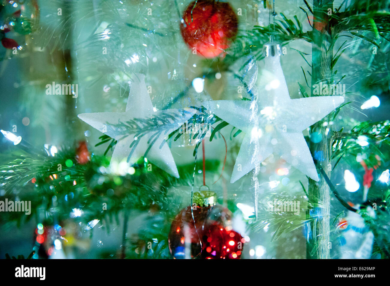 Twinkly vivace, Christmassy strati con aghi di pino, baubles, stelle e luci. Immagini Stock