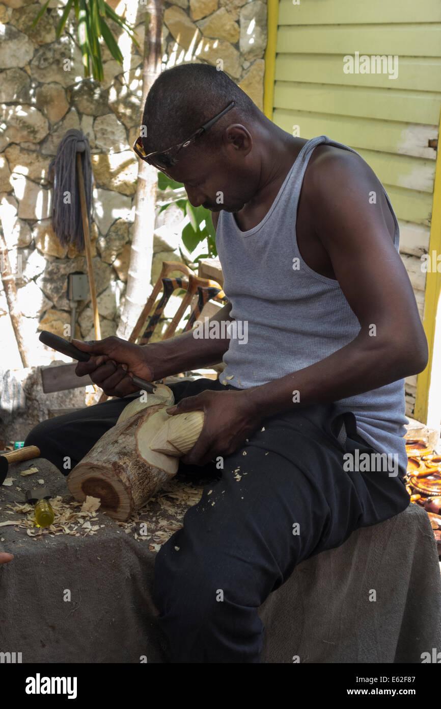 Artigiano carving statua in legno, il Nassau Il Mercato della paglia, Isola Provvidenza, le Bahamas Immagini Stock