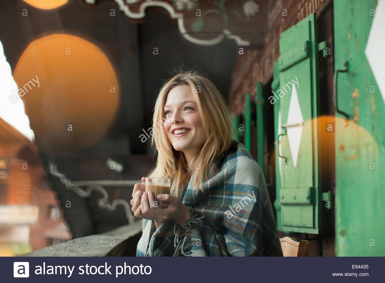Donna sorridente avvolto in una coperta e di bere il caffè sul portico di cabina Immagini Stock