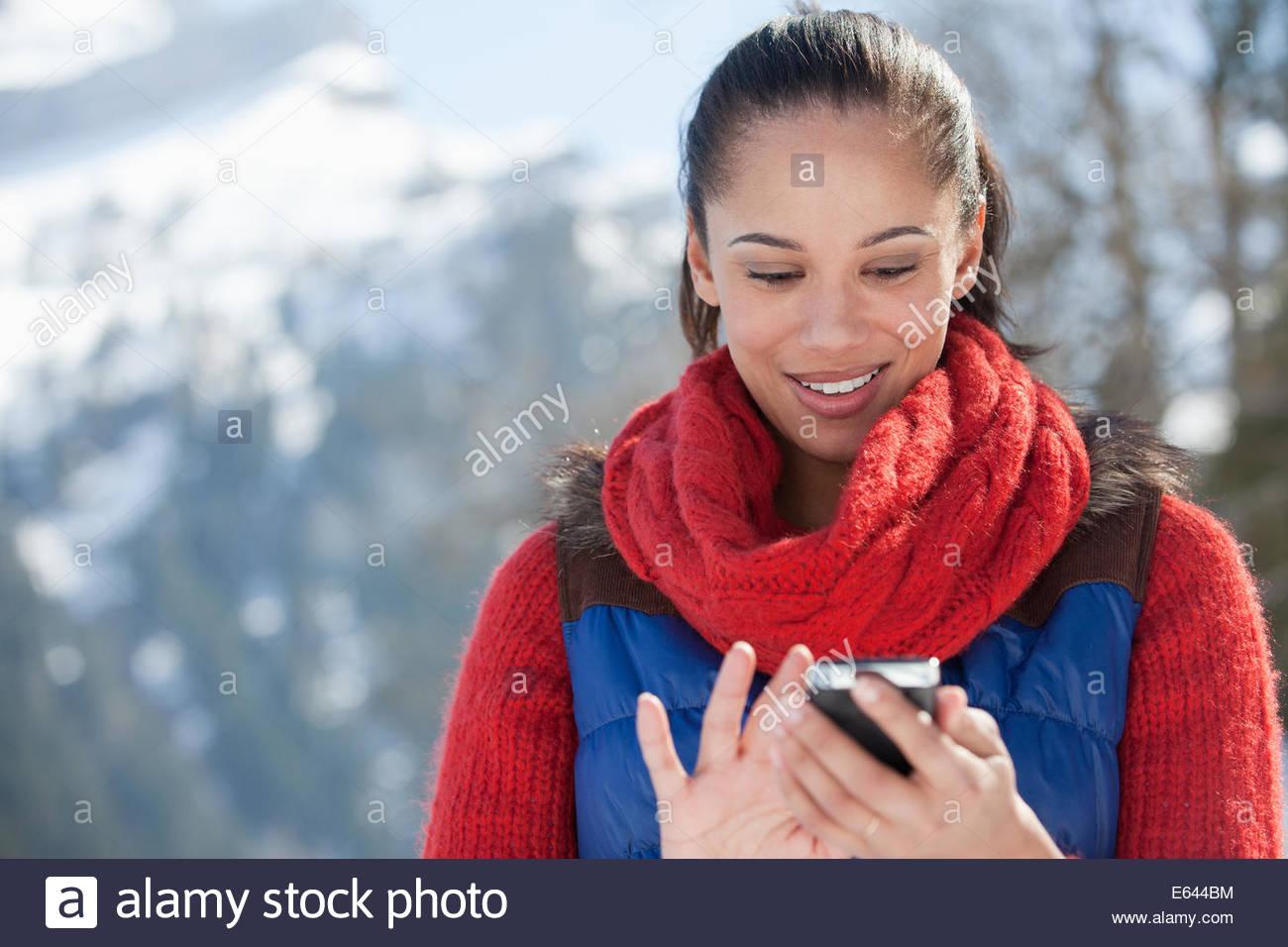 Donna sorridente controllo telefono cellulare Immagini Stock