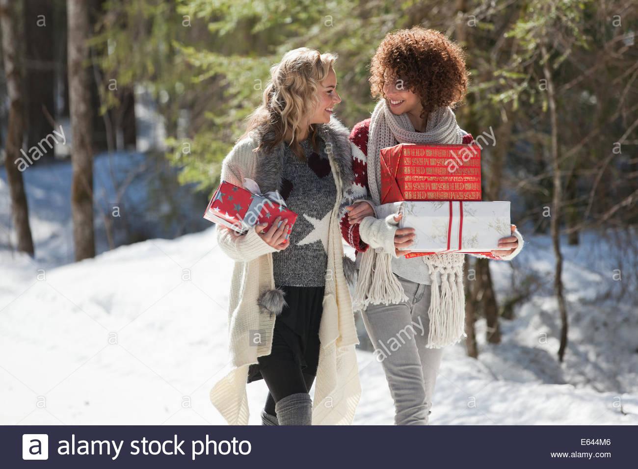 Due donne che portano doni all'aperto in inverno Immagini Stock