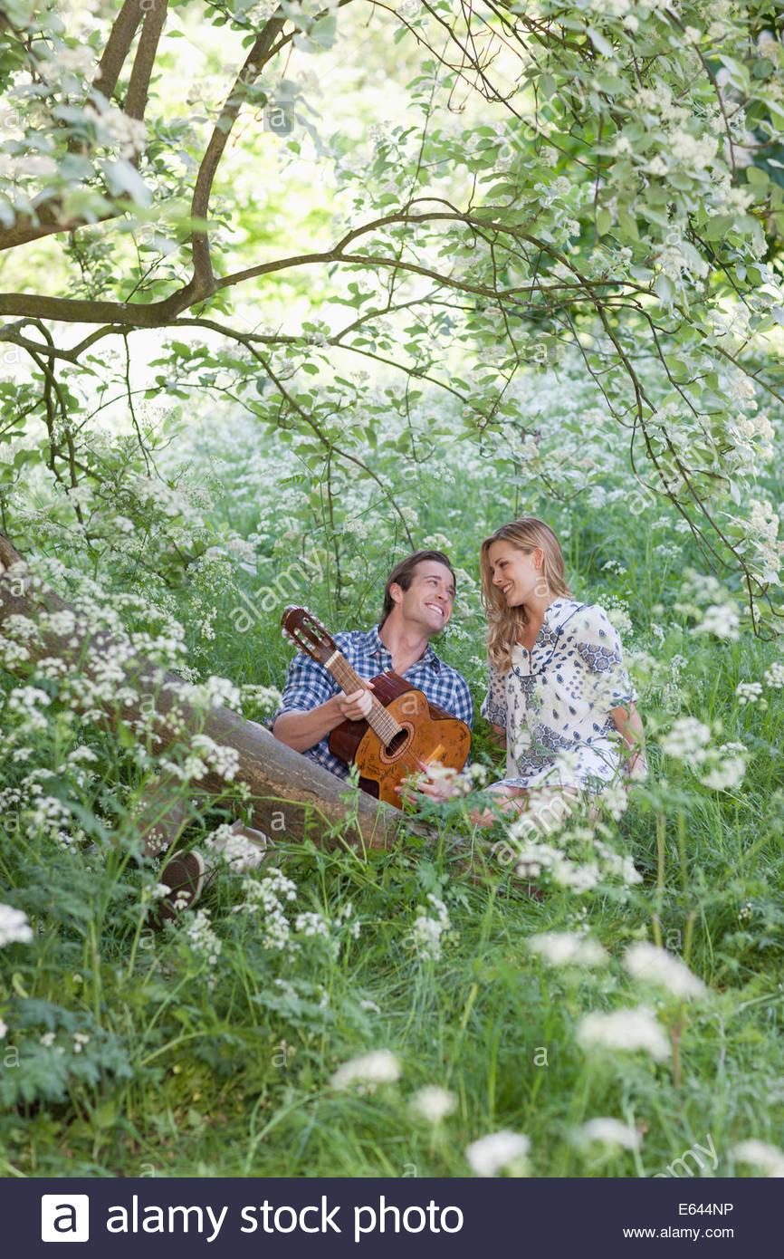 Uomo a suonare la chitarra per ragazza in foresta Immagini Stock