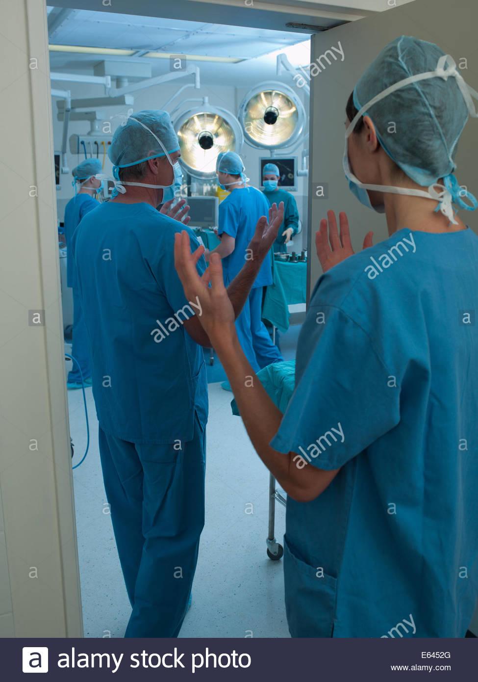 I chirurghi con le mani pulite di entrare in sala operatoria Immagini Stock