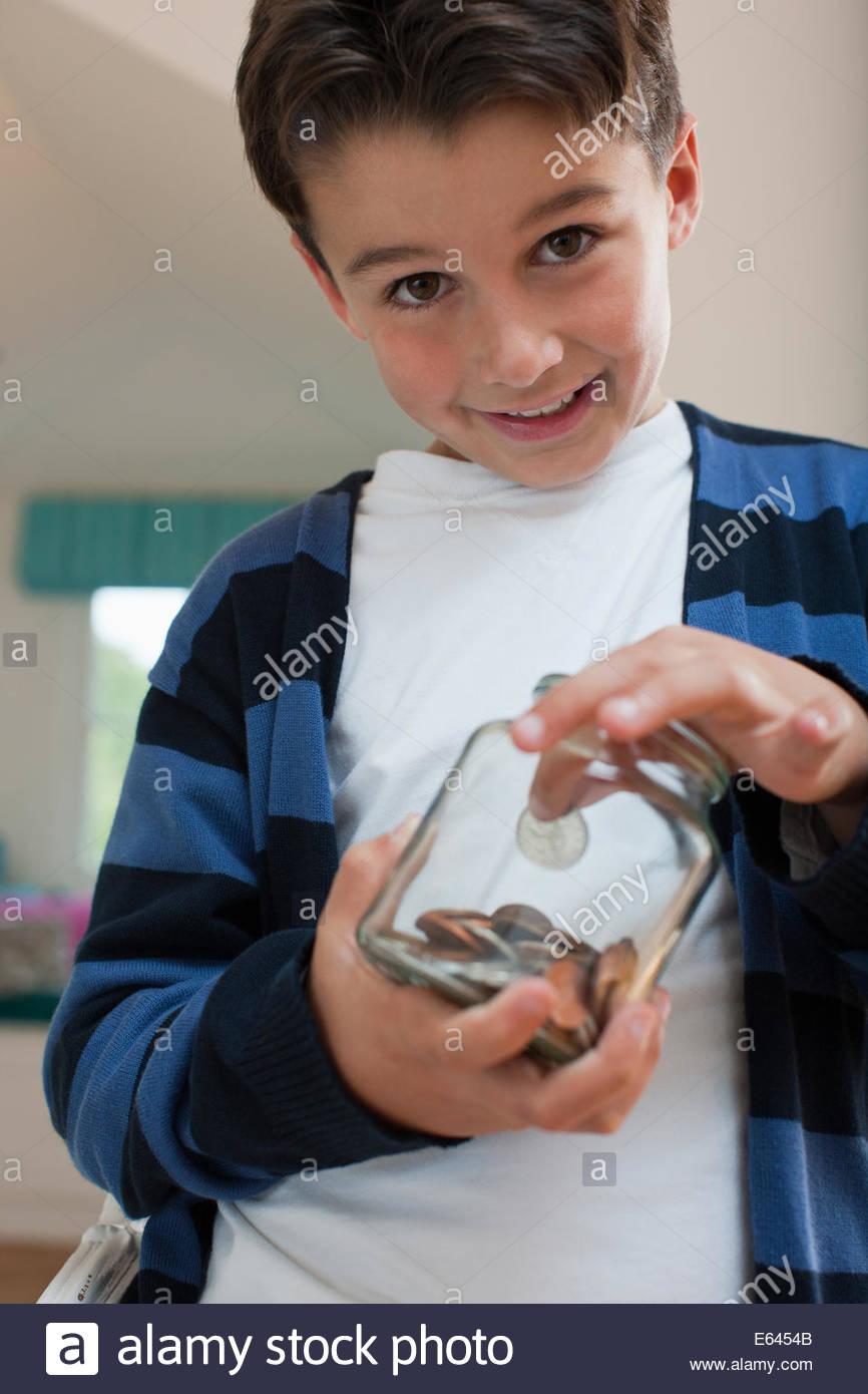 Ragazzo con un vasetto di monete Immagini Stock