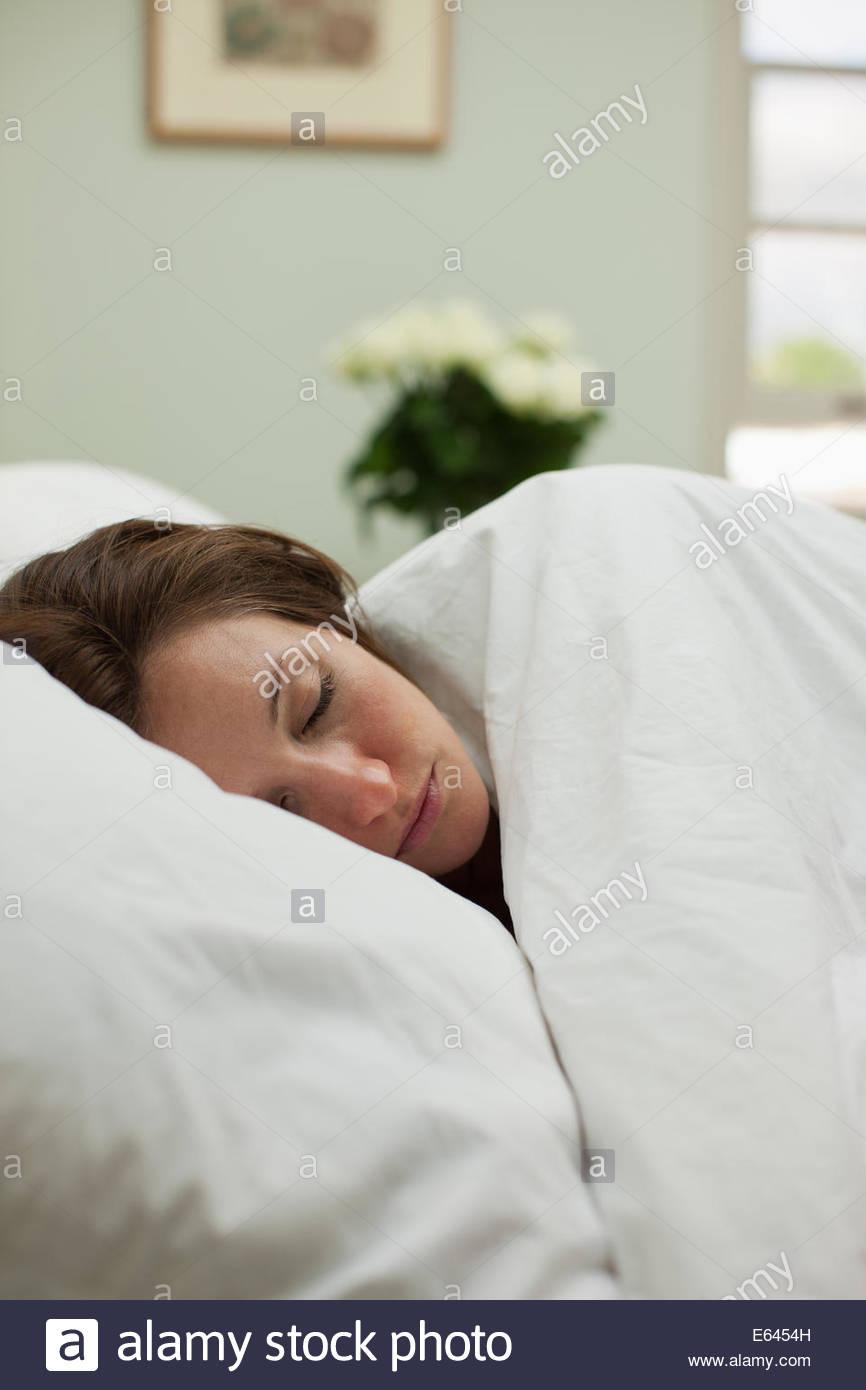 Malati donna che dorme nel letto sotto coperta Immagini Stock