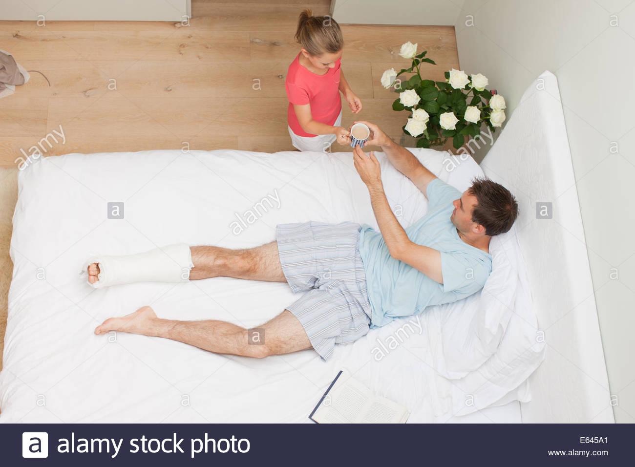 Figlia di portare il caffè al Padre con la gamba rotta Immagini Stock