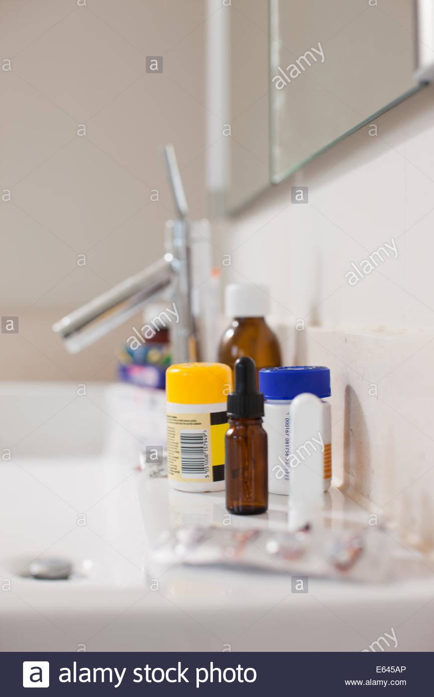 Articoli da toeletta e un farmaco sul lavandino in bagno Immagini Stock
