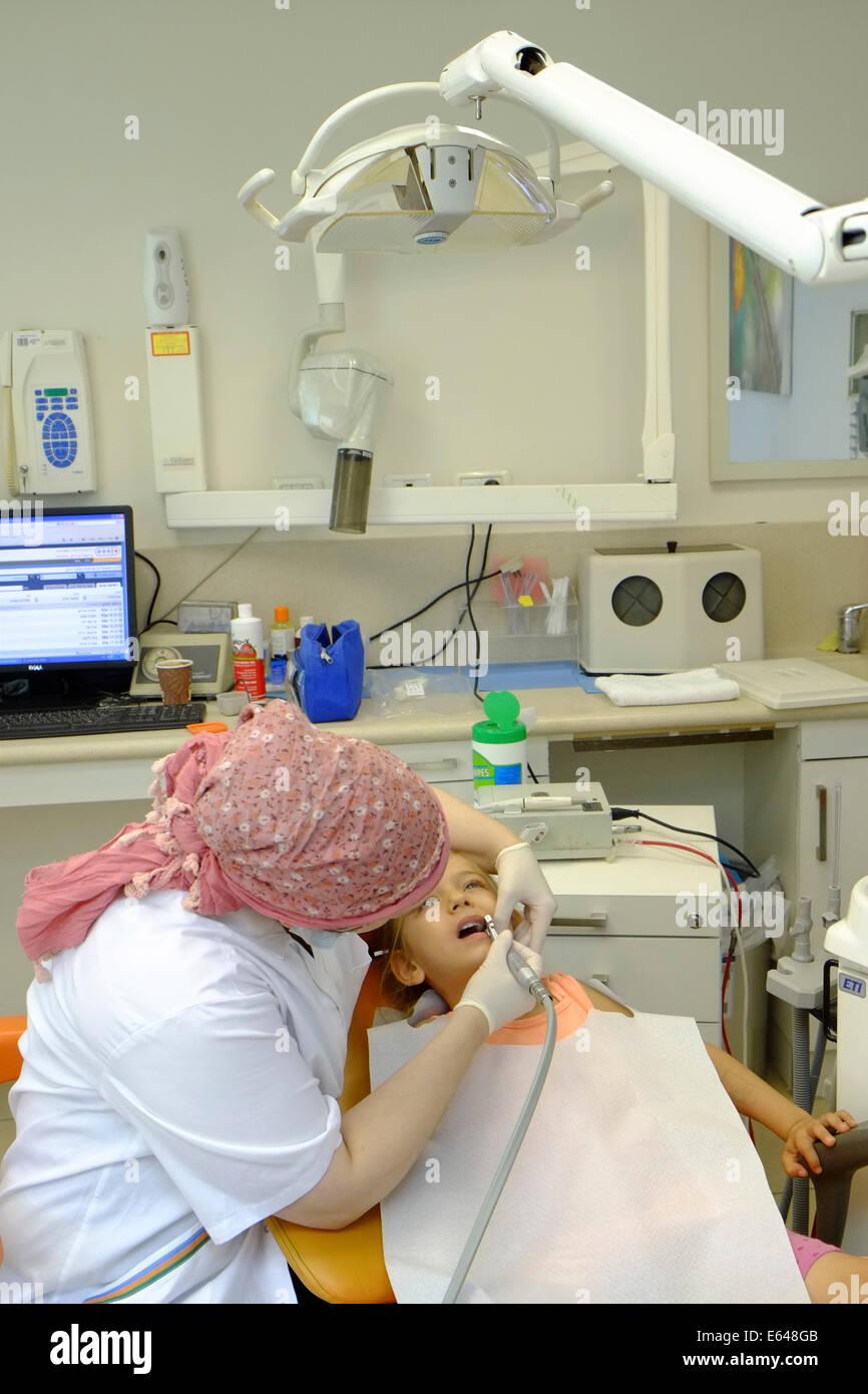 Giovane ragazza ha i suoi denti puliti mediante un igienista dentale presso il dentista Immagini Stock