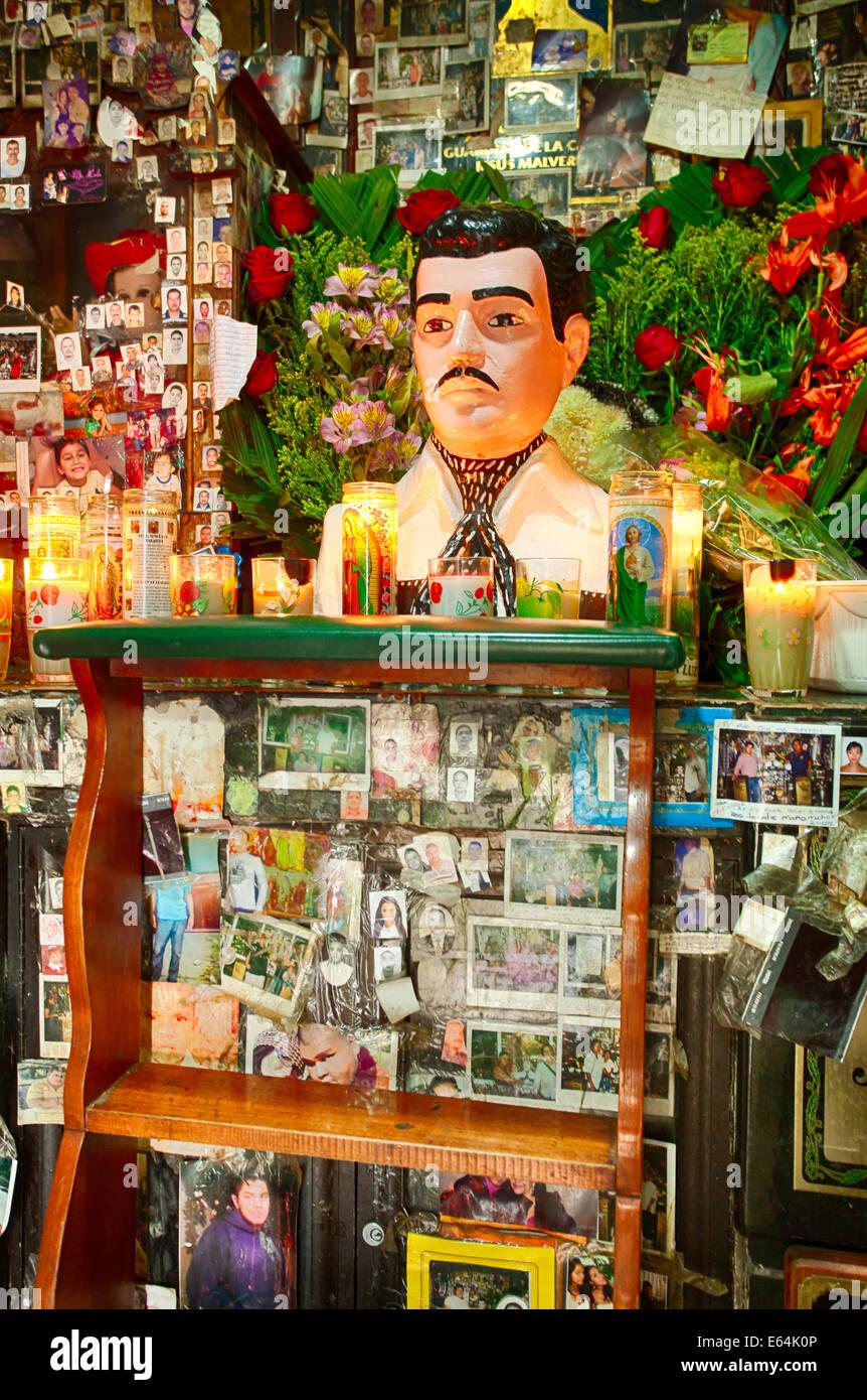 Le fotografie, i messaggi di ringraziamento e fiori circondano un santuario dedicato a malverde, patrono del traffico Immagini Stock