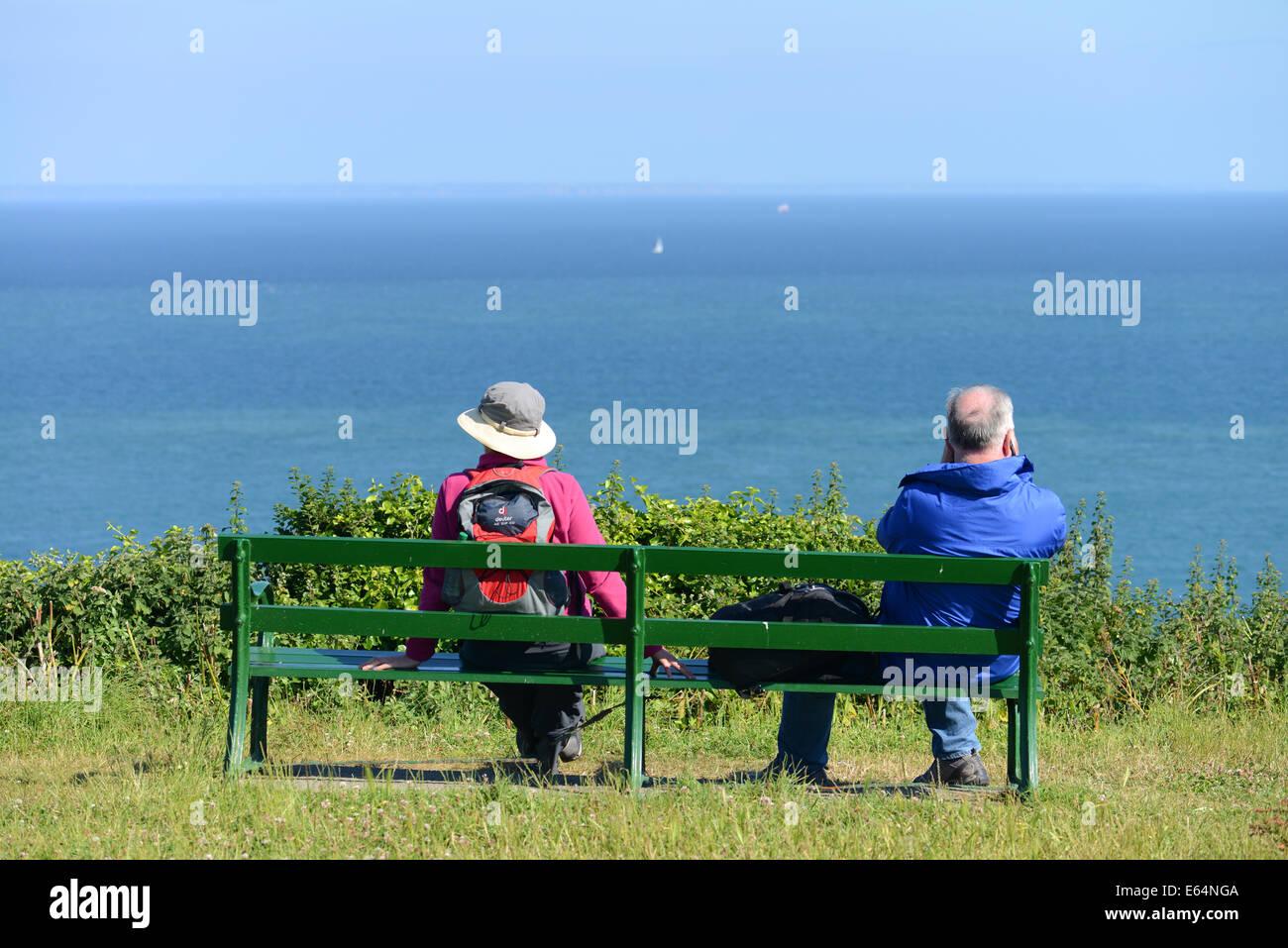 Un giovane che guarda al mare mentre si è seduti su una panchina a Jerbourg Point, Guernsey, Isole del Canale, Immagini Stock