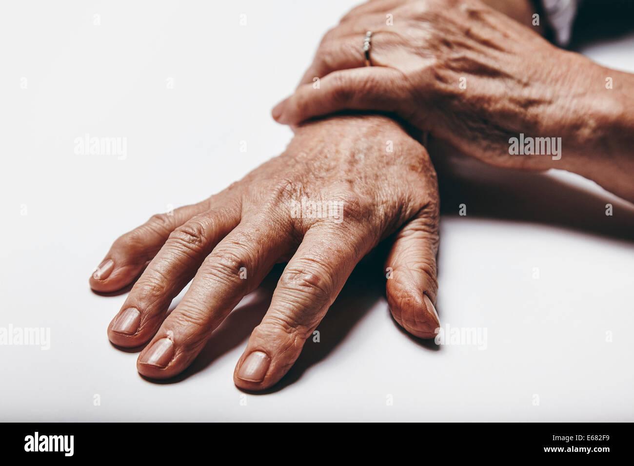 Macro di vecchia donna le mani su una superficie di colore grigio. Concentrarsi sulle dita di senior femminili. Immagini Stock
