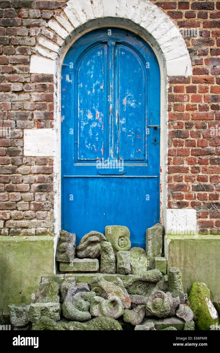 Vecchio Blu porta in rosso di un muro di mattoni con ornamenti di pietra di fronte. Immagini Stock
