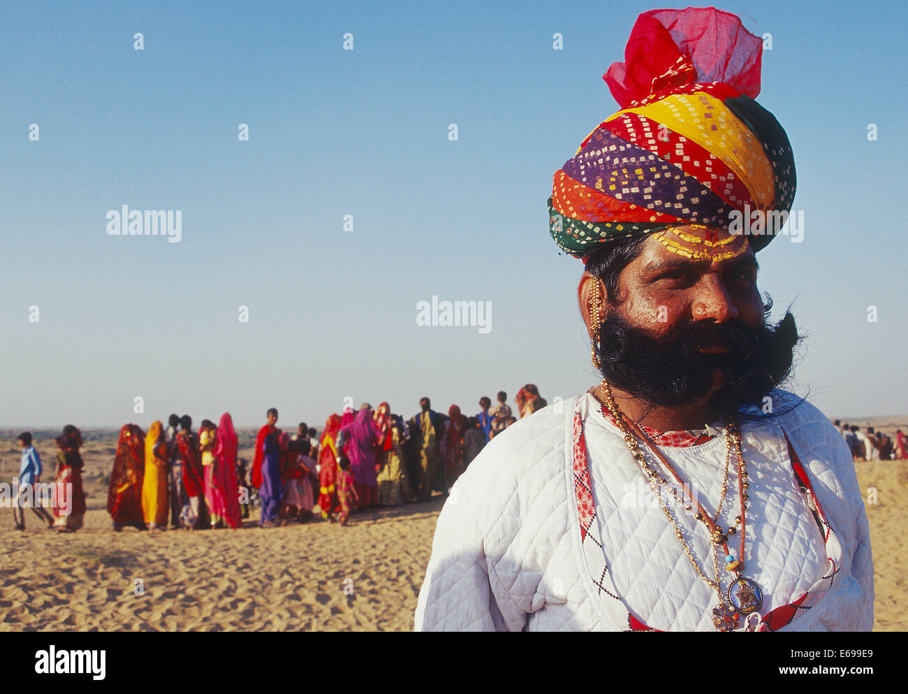 Tradizionalmente vestito uomo indù. Egli appartiene alla classe di Rajput. In background, donne locali sono Immagini Stock