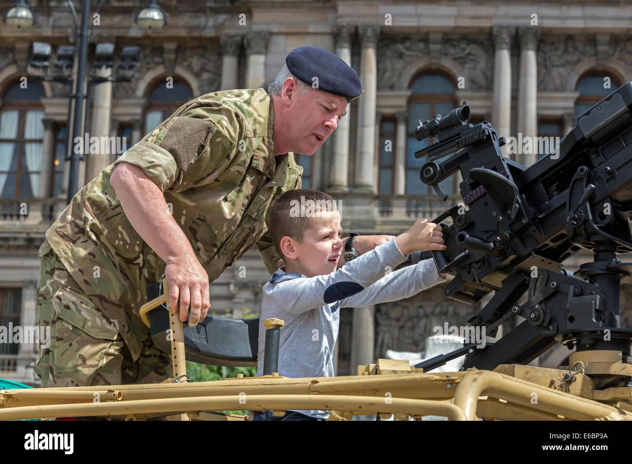 Ragazzo giovane essendo dato istruzioni su come usare la pistola della macchina durante un display militare e parade, Immagini Stock