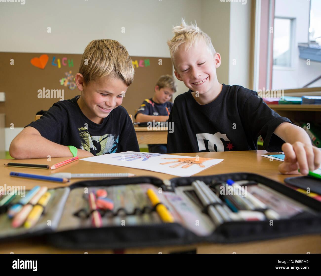 Sorridente bambini seduti in una scuola primaria classe durante una lezione di disegno, Reith im Alpbachtal, distretto Immagini Stock